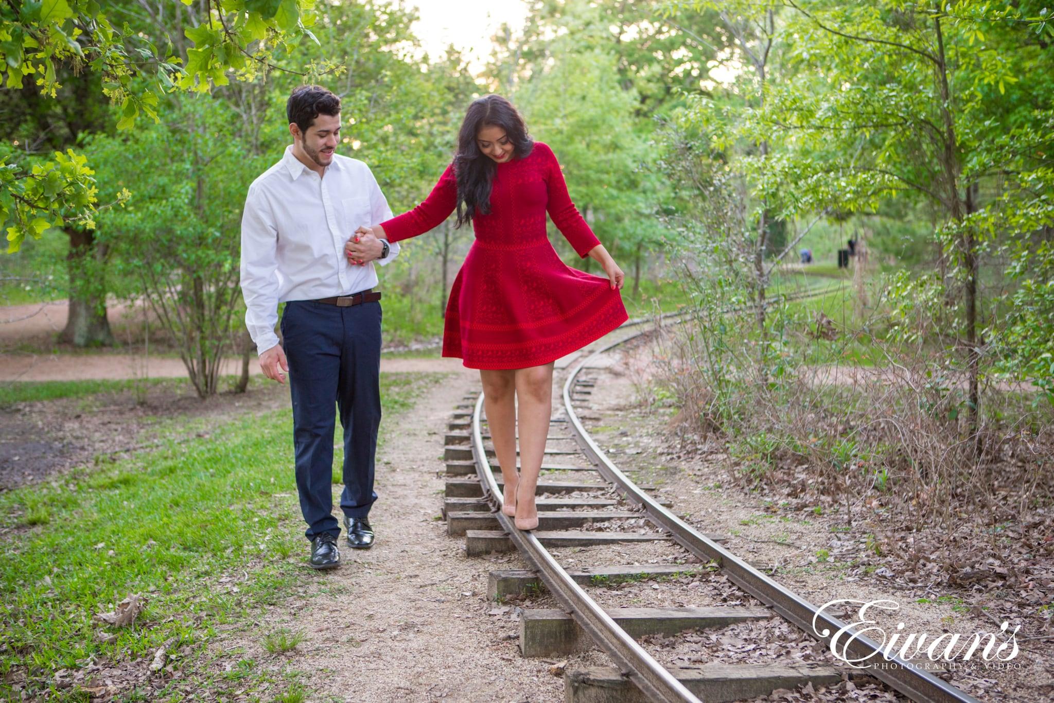 image of engaged couple walking along train tracks