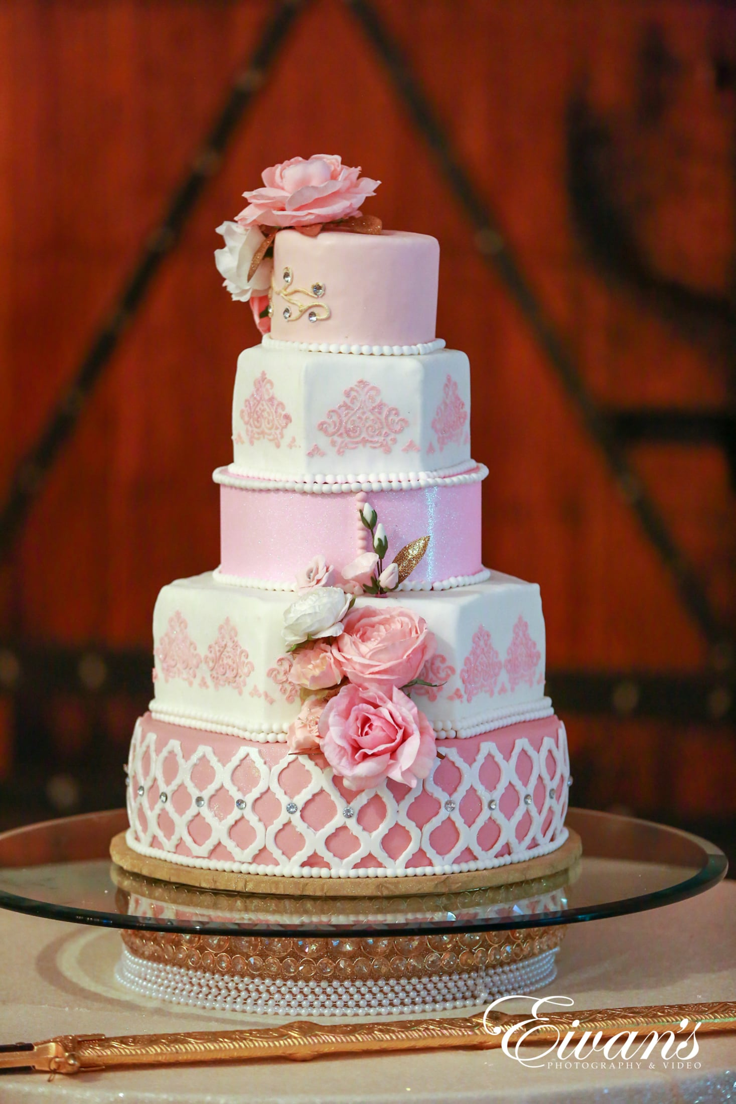 image of a five teared cake of pink and white