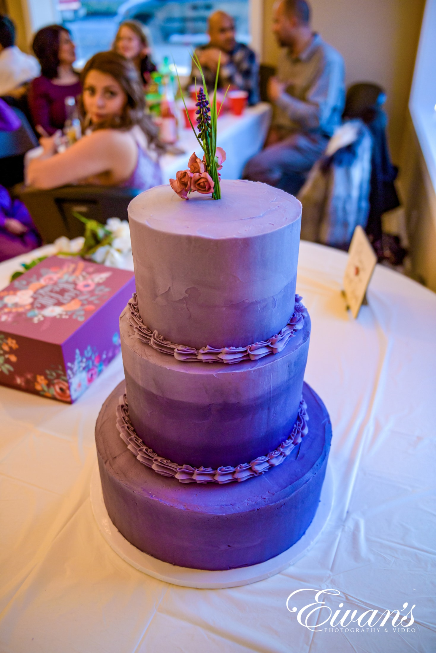 image of a three teared cake with purple frosting on it
