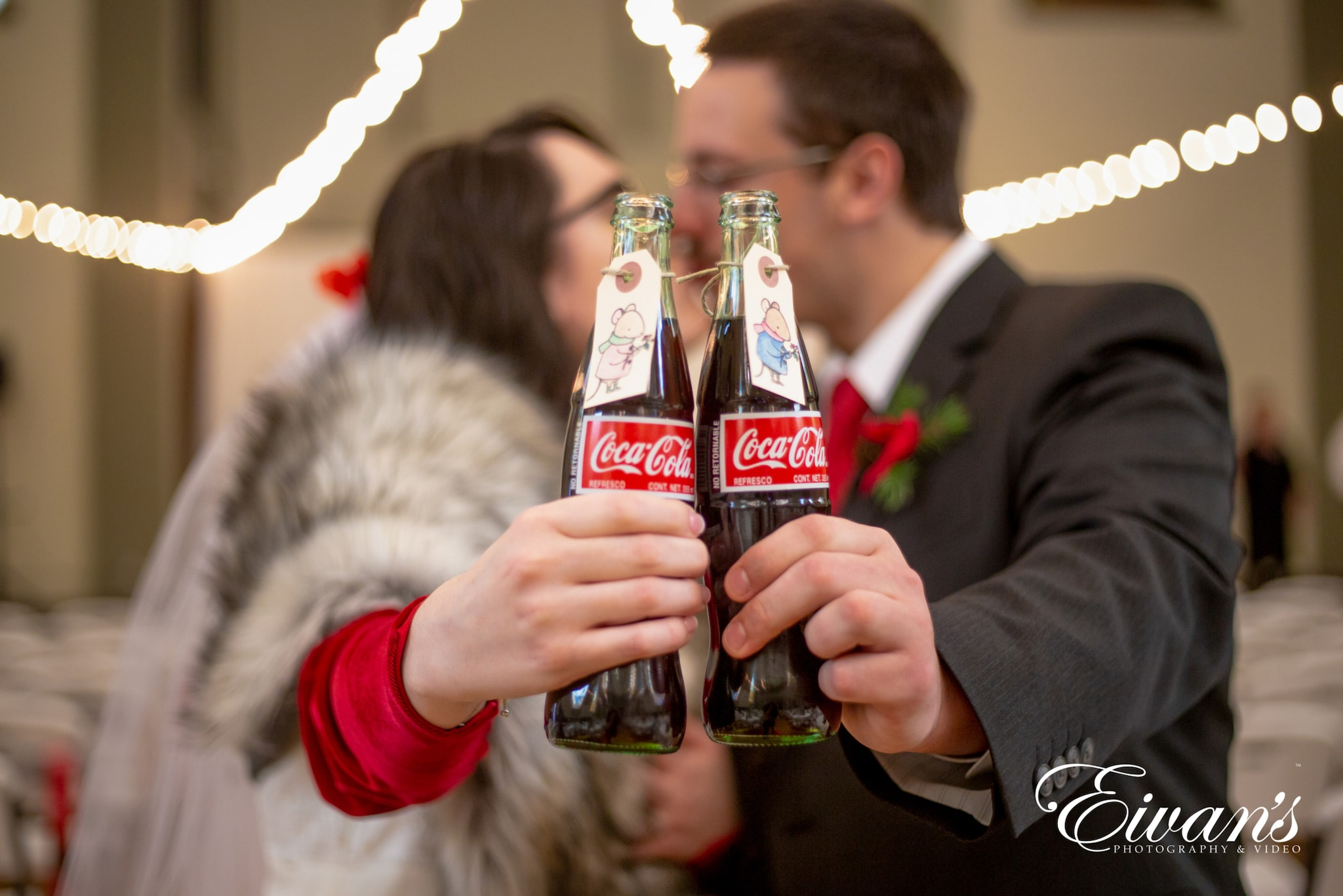 image of engaged couple kissing and cheering a coke