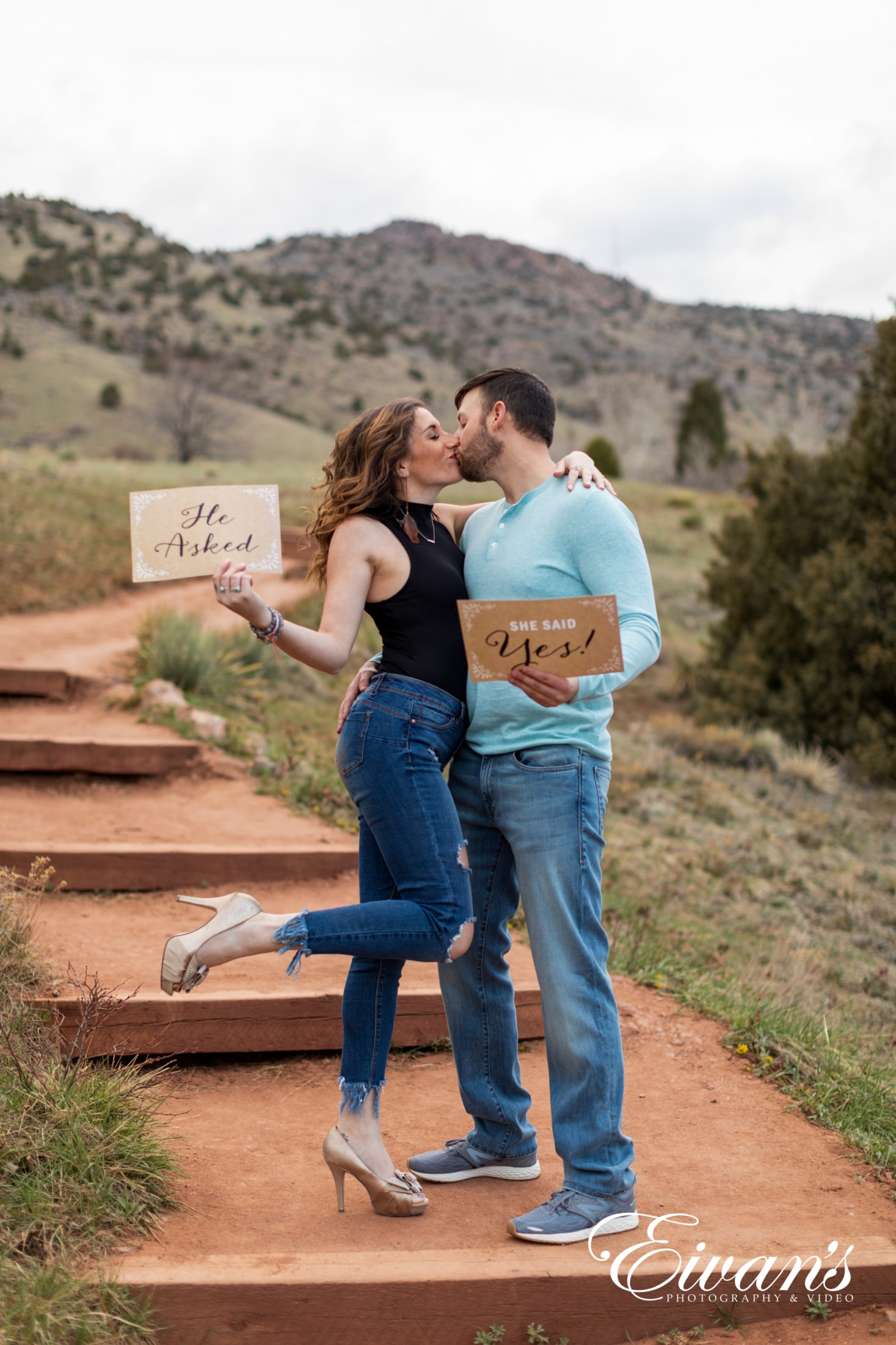 image of an engaged couple holding up signs