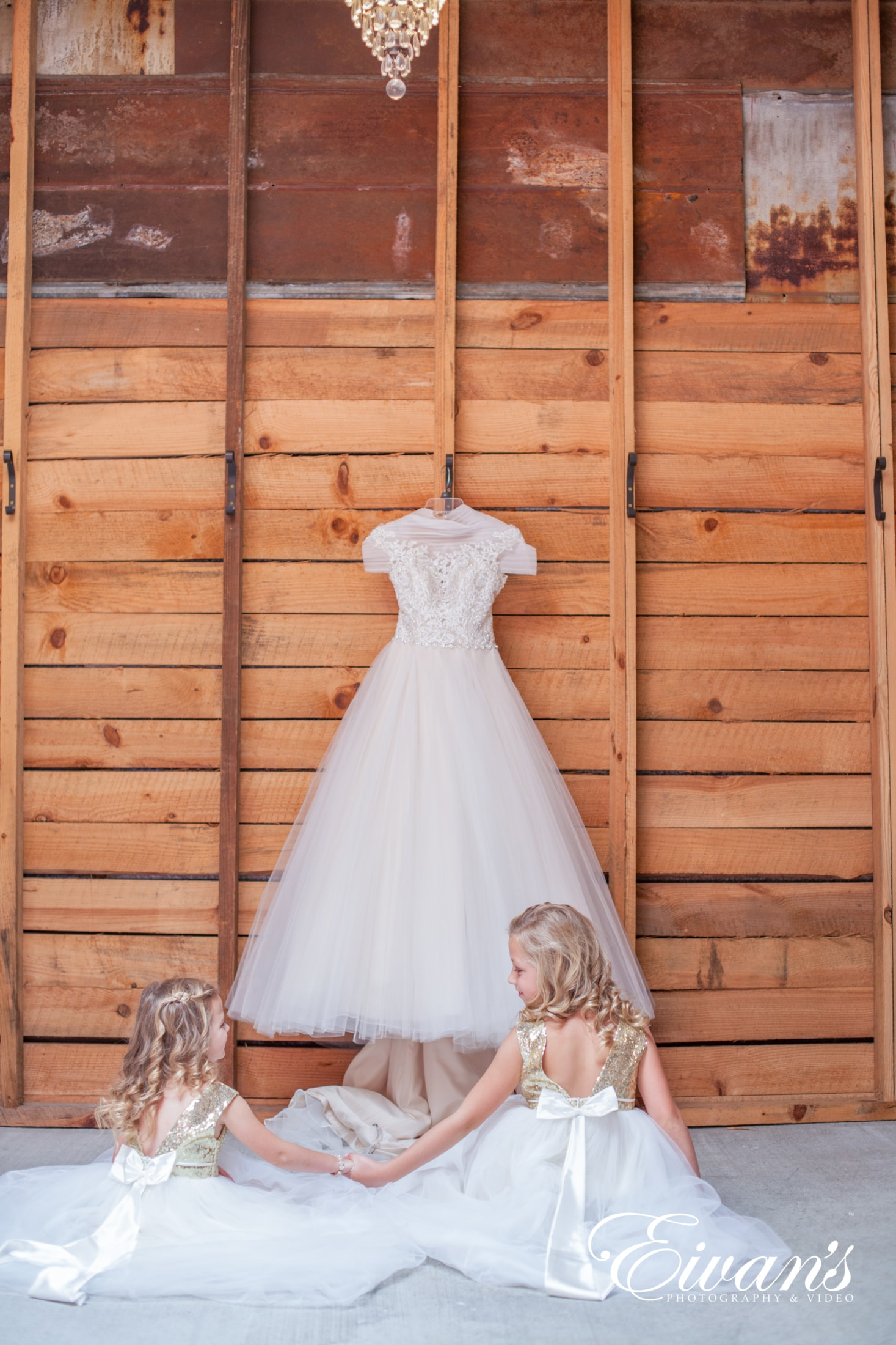 image of two young girls sitting on the floor in front of a wedding dress