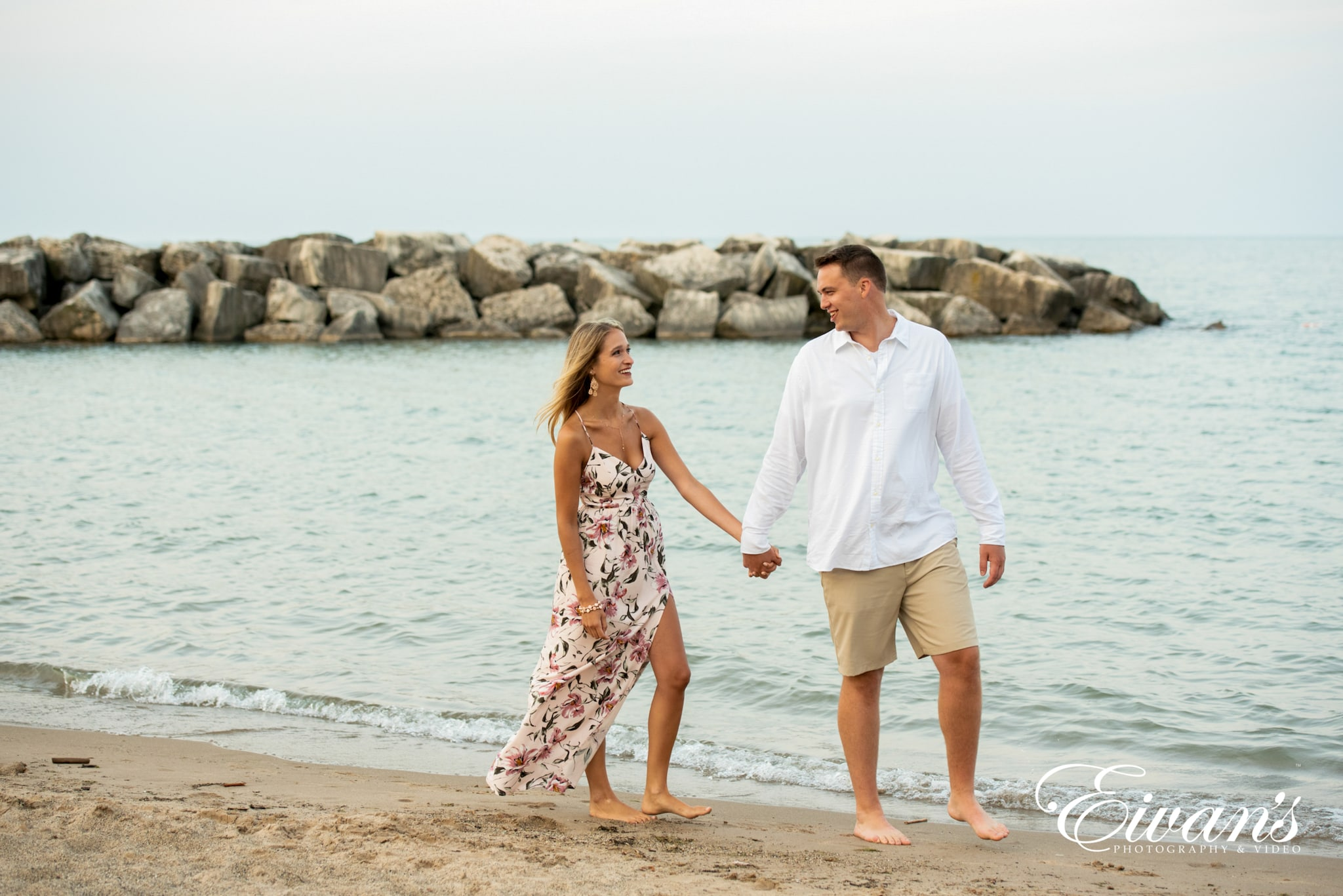 image of engaged couple walking on the beach