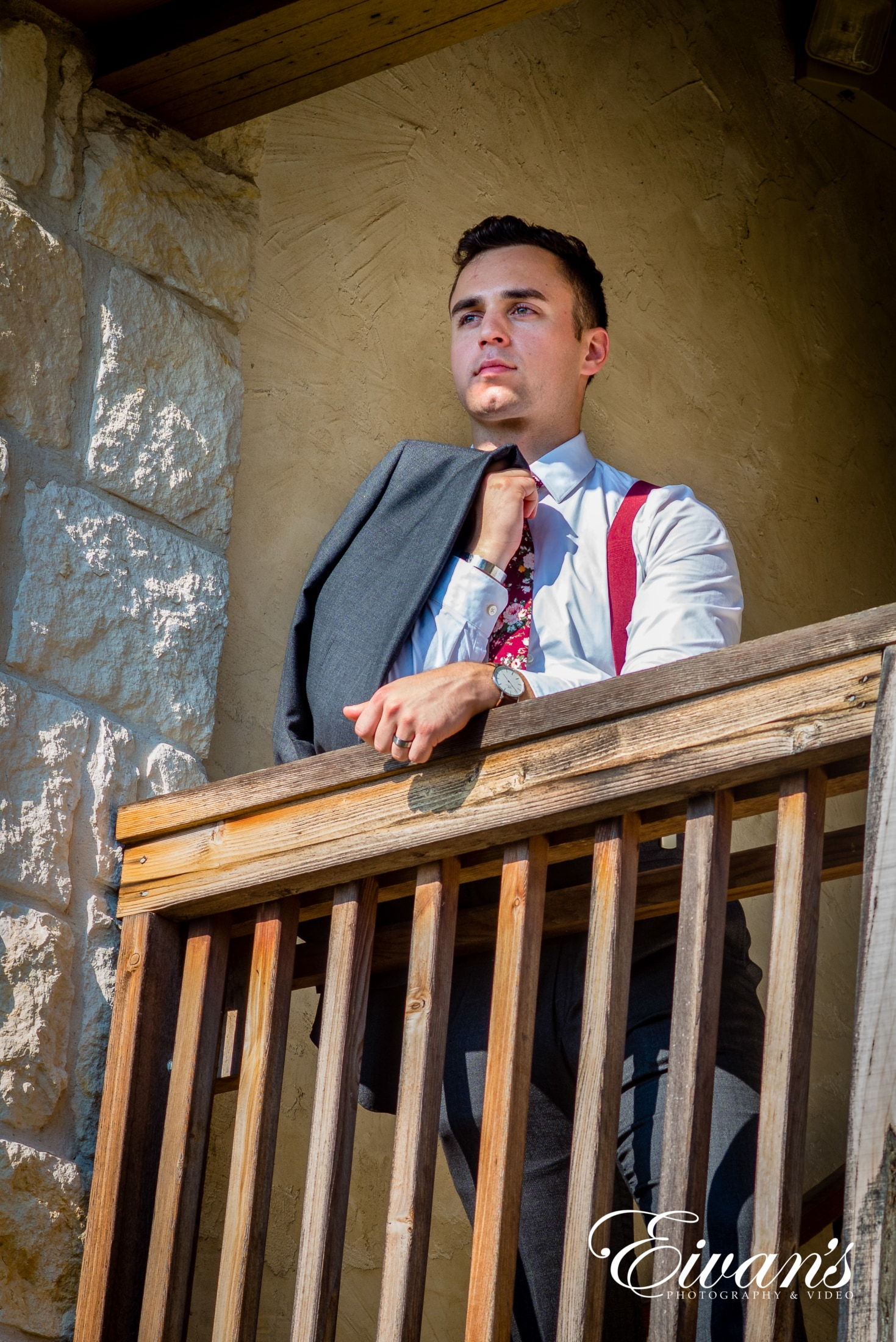 image of a groom looking off the balcony