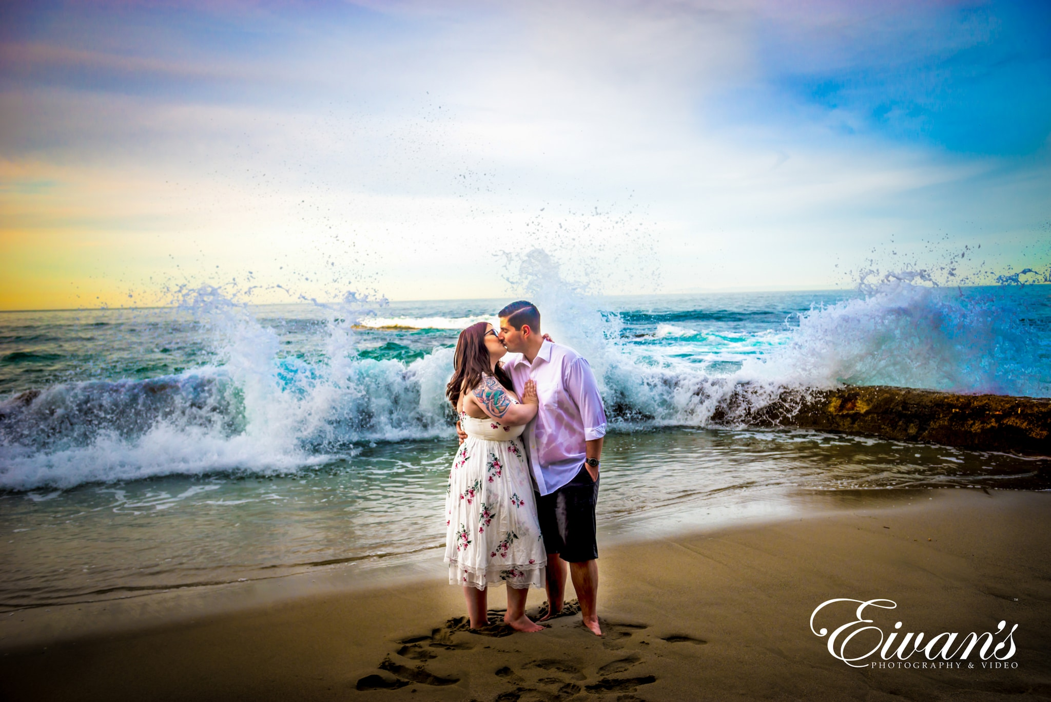 image of an engaged couple in front of waves