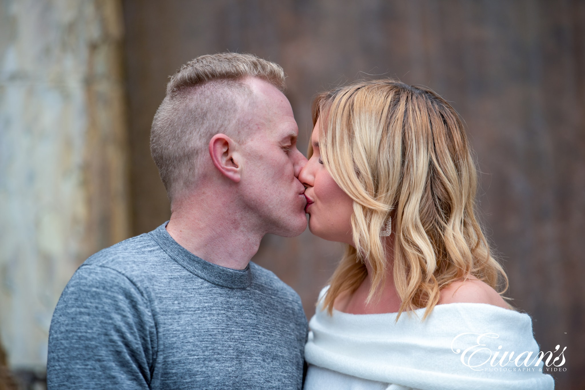 image of engaged man and woman kissing