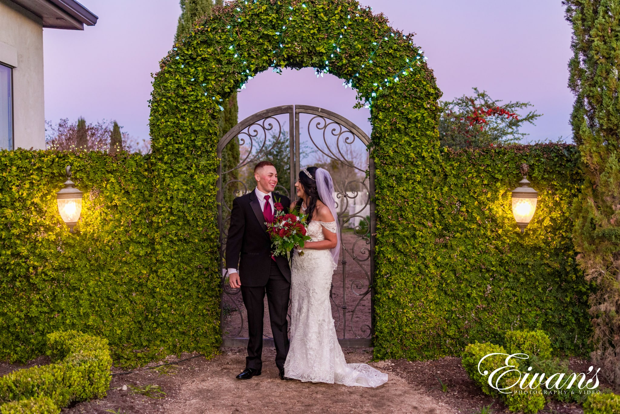 image of a married couple in front of a greenery archway