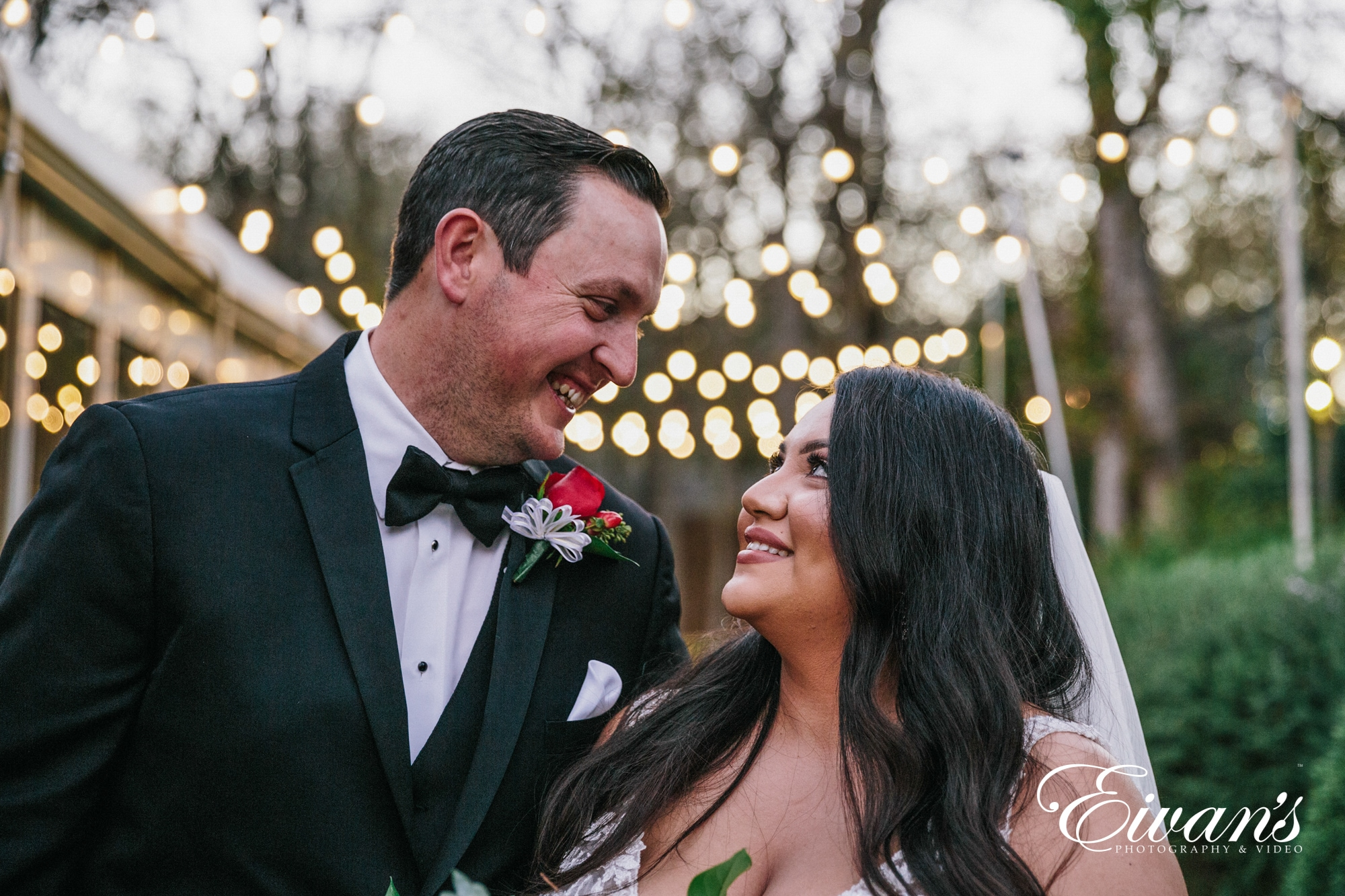 image of a bride and groom looking into each others eyes and smiling under fairy lights