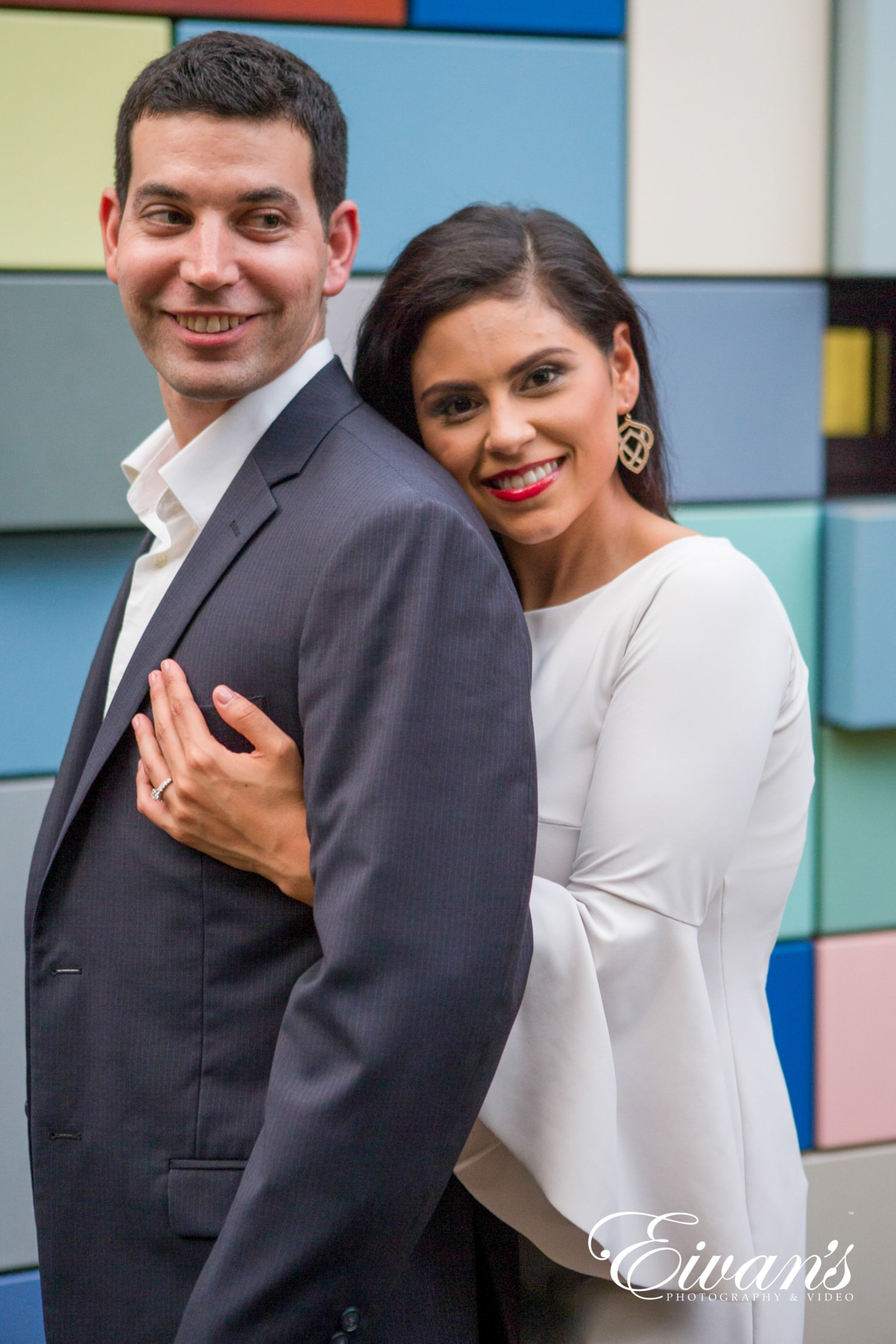 image of engaged man and woman, woman is hugging man from behind in front of a backdrop of colored squares