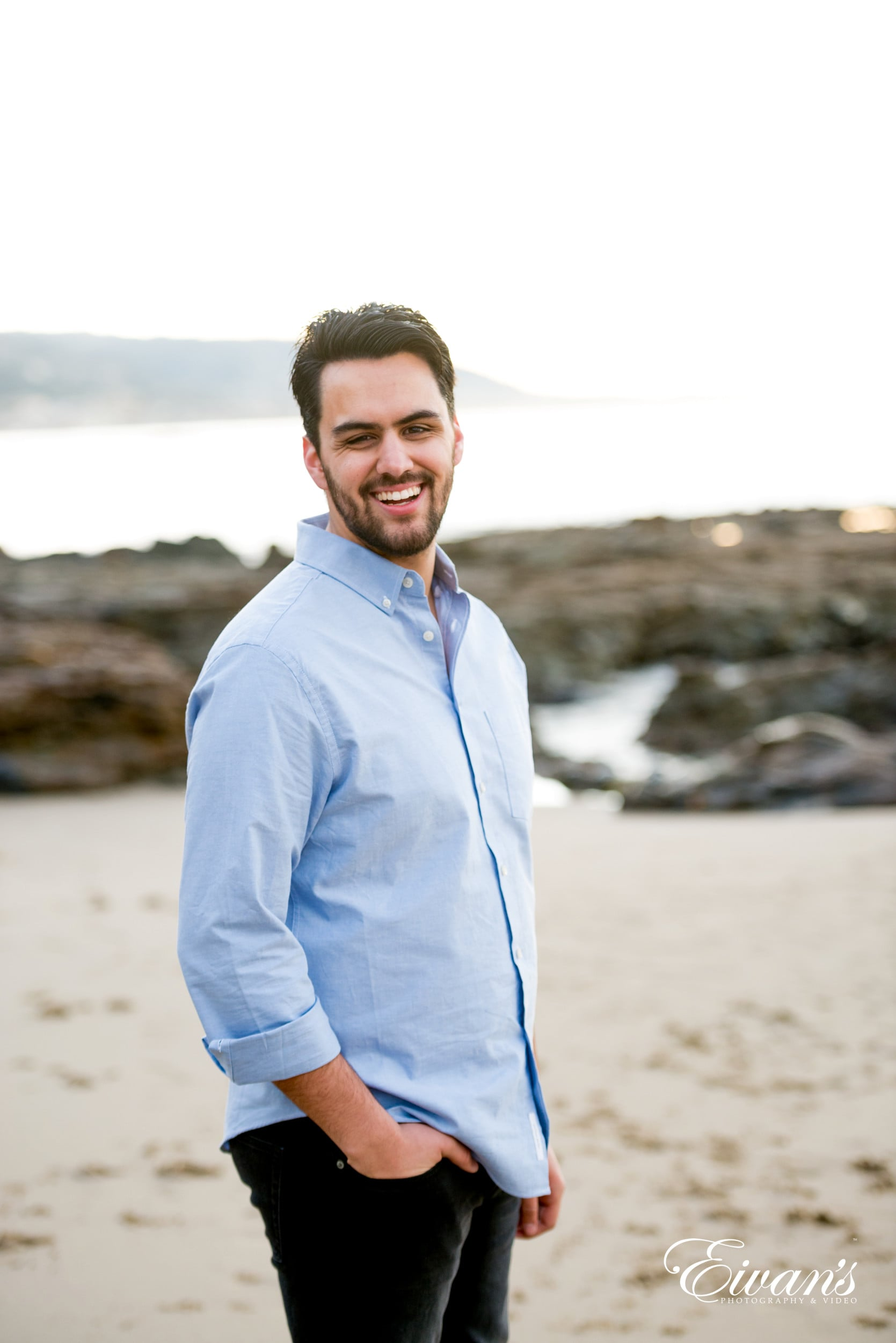 man in blue dress shirt standing on white sand during daytime