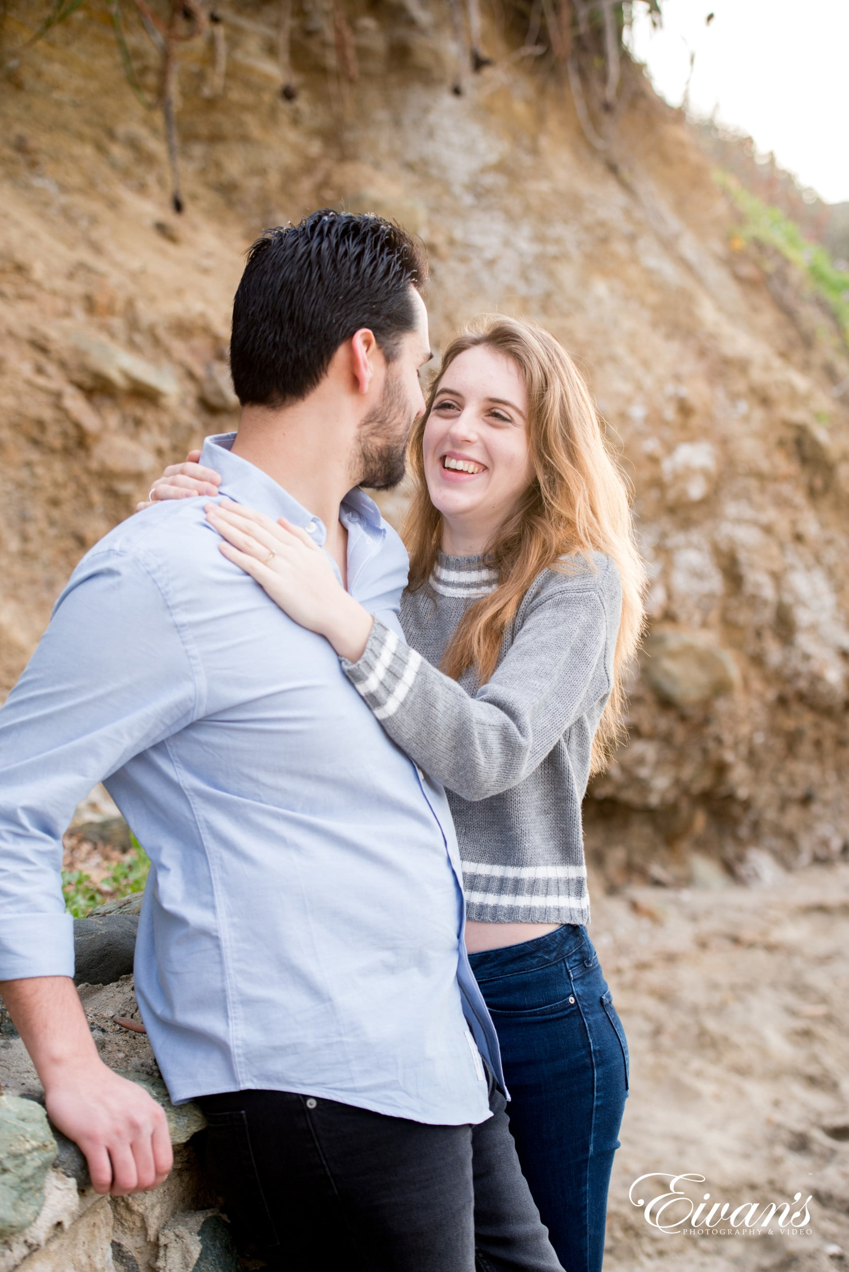 man in gray sweater hugging woman in white long sleeve shirt