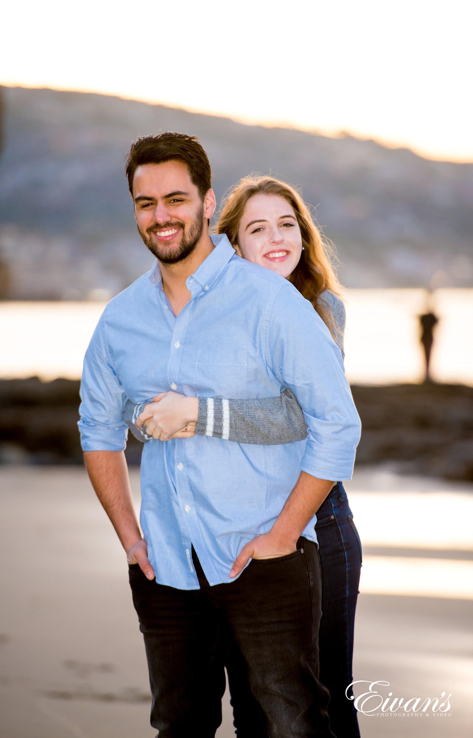 man in blue dress shirt hugging woman in gray long sleeve shirt