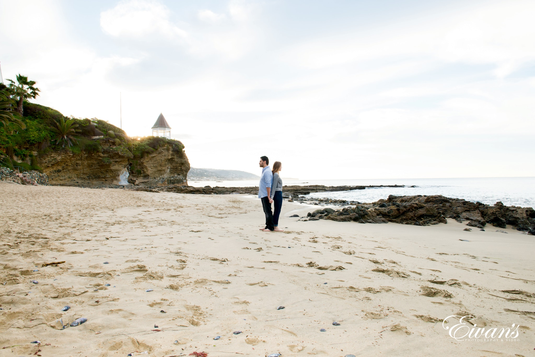 man in white long sleeve shirt and black pants walking on beach during daytime