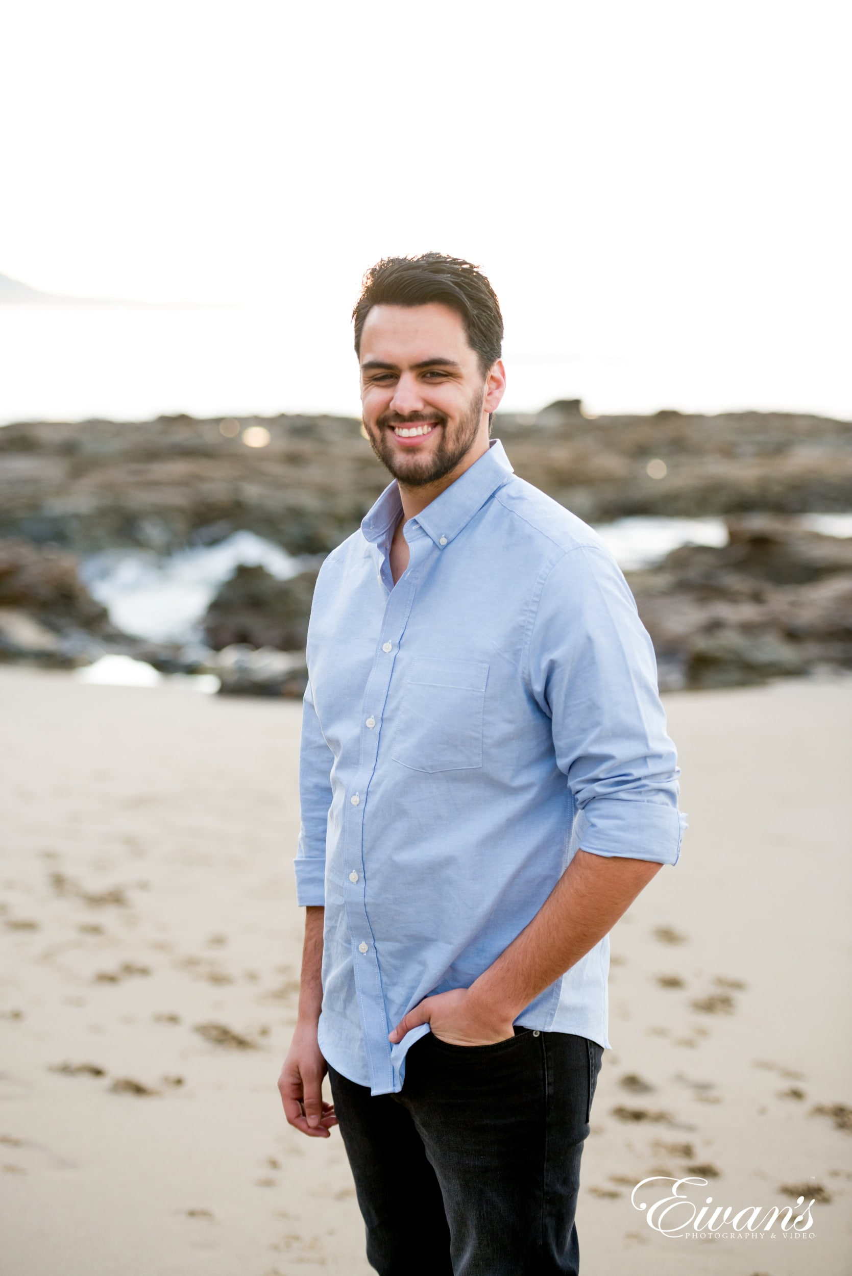 man in blue dress shirt standing on beach during daytime