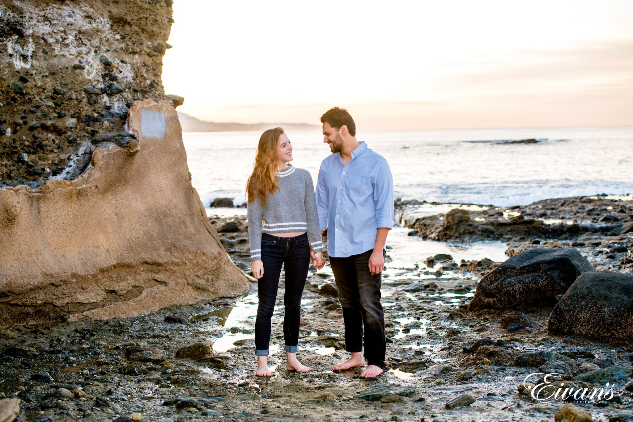man and woman standing on rocky shore during daytime