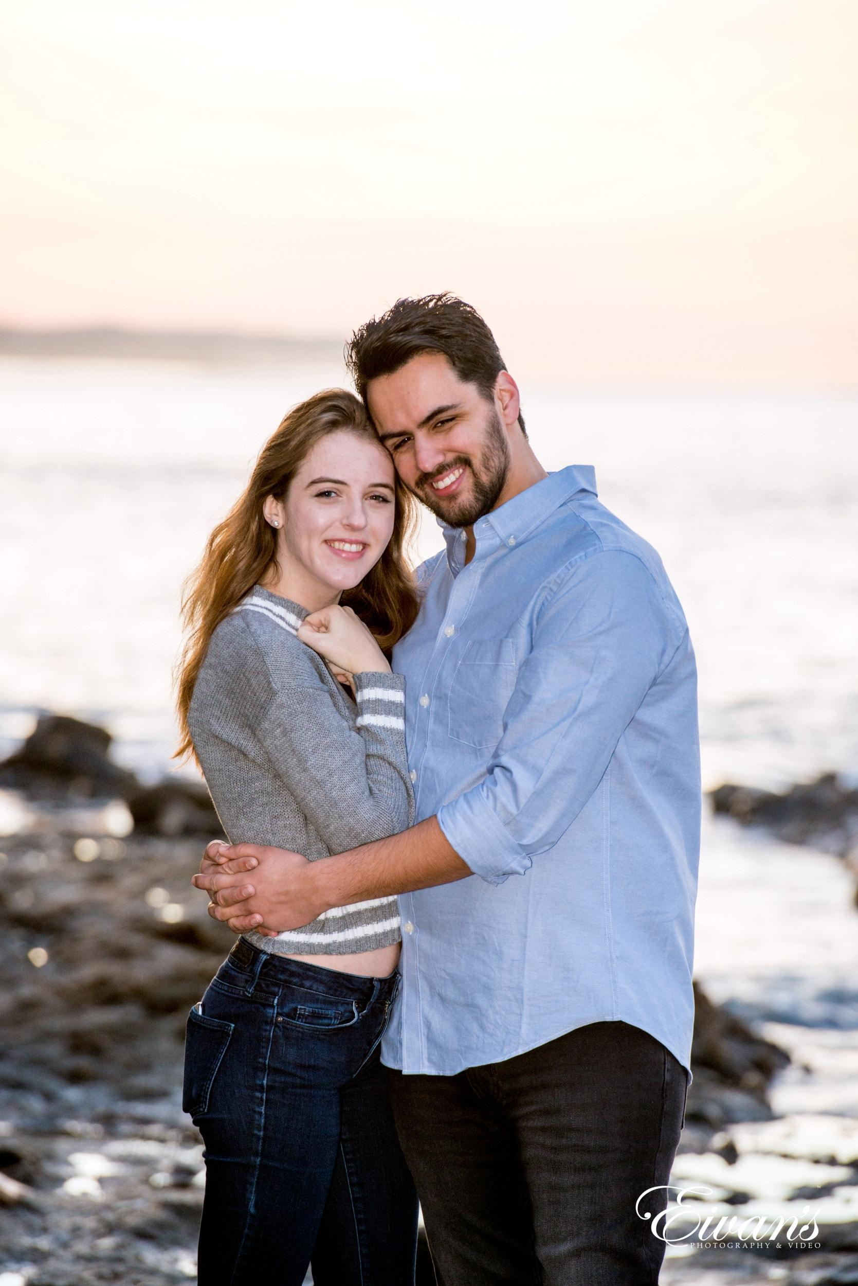 man in blue dress shirt hugging woman in black dress