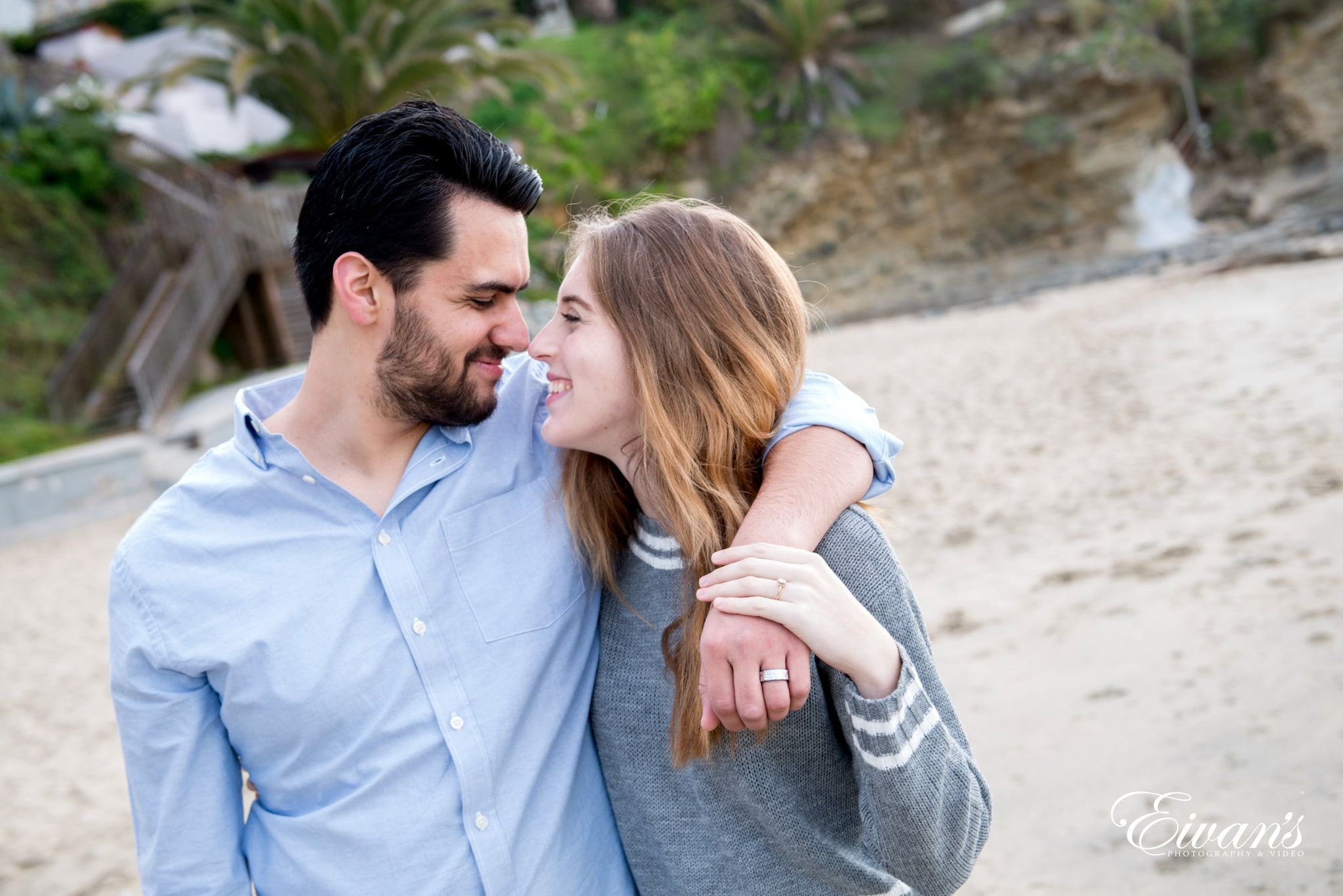 man in blue dress shirt kissing woman in gray sweater