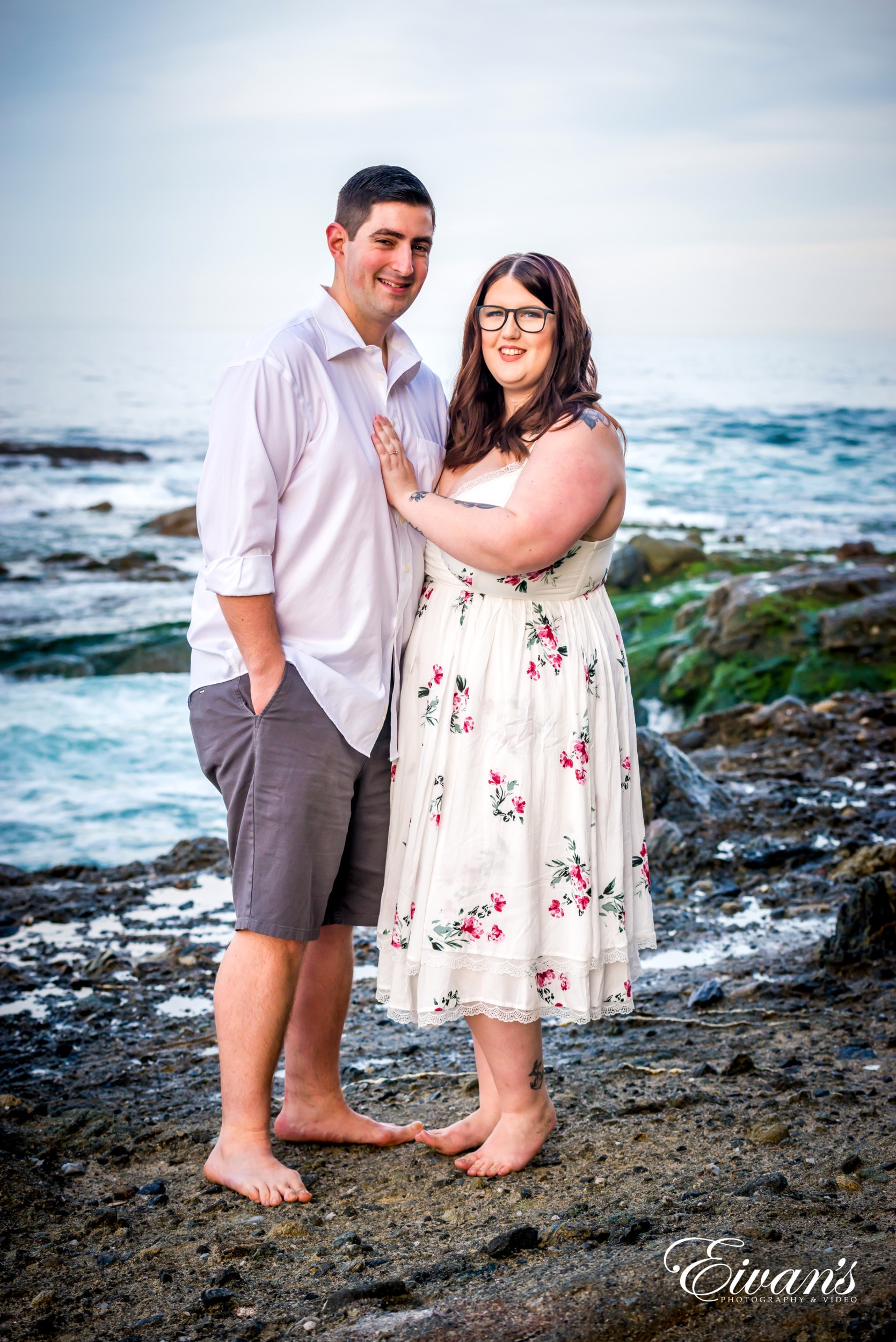 man in white dress shirt beside woman in white and pink floral dress standing on beach