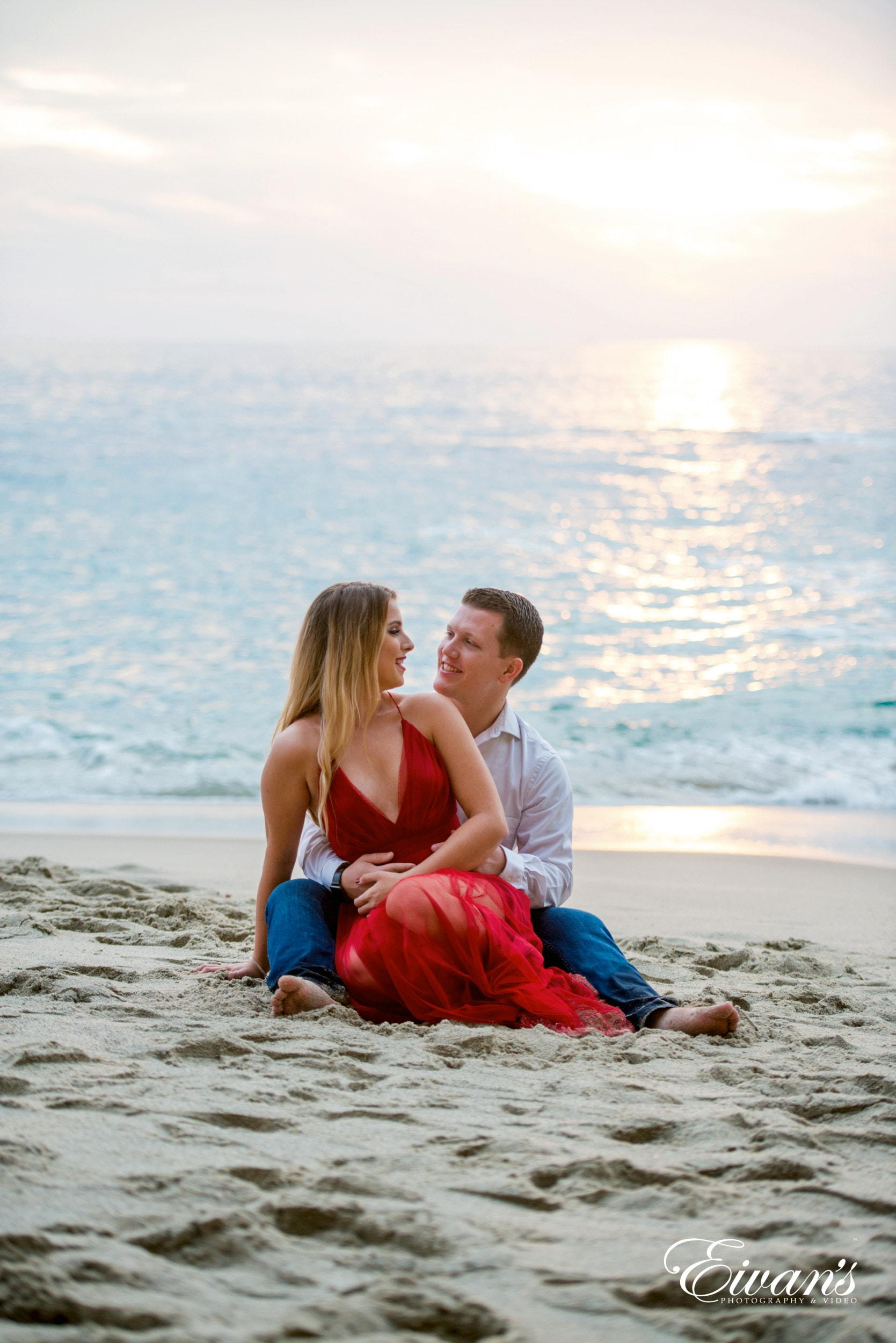 man and woman sitting on beach during daytime