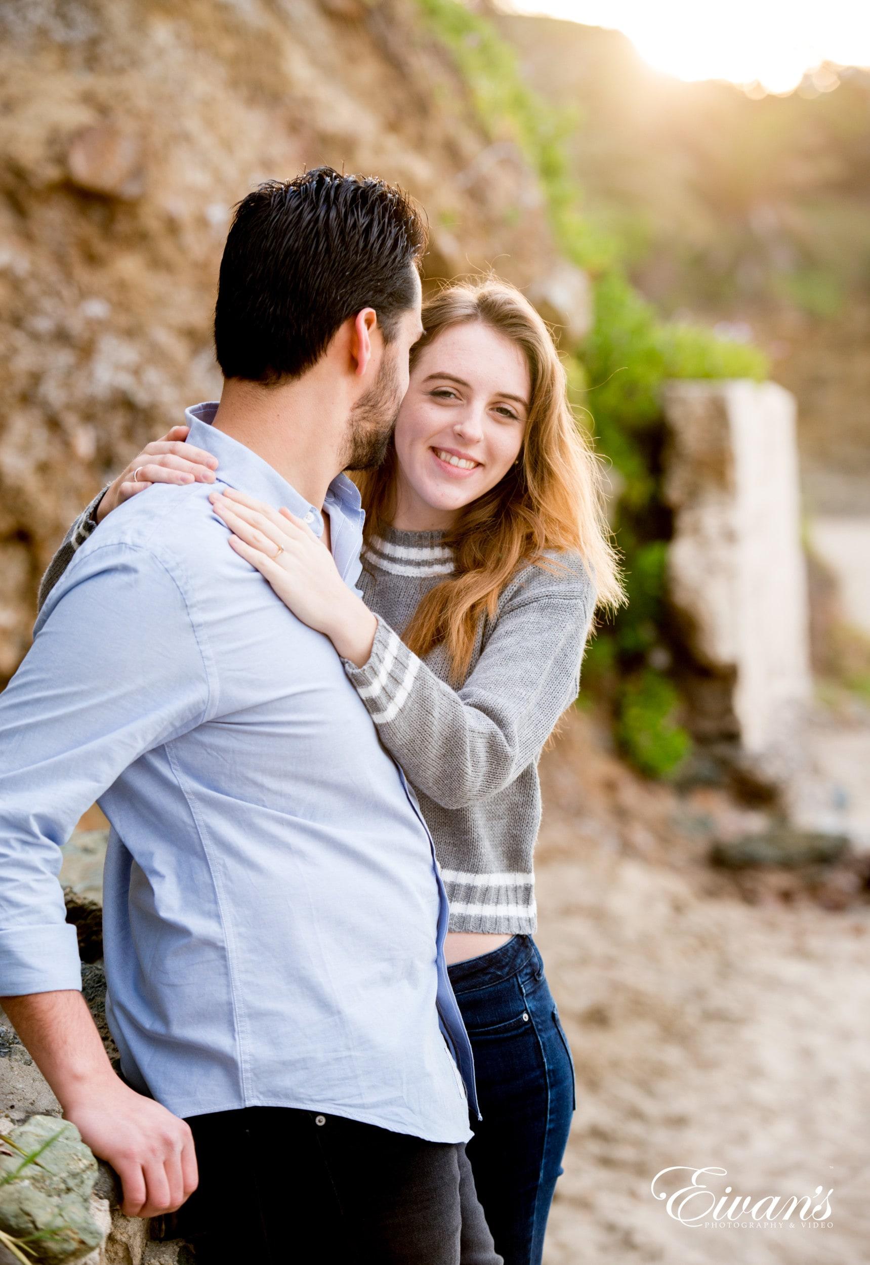 man in gray long sleeve shirt hugging woman in gray long sleeve shirt
