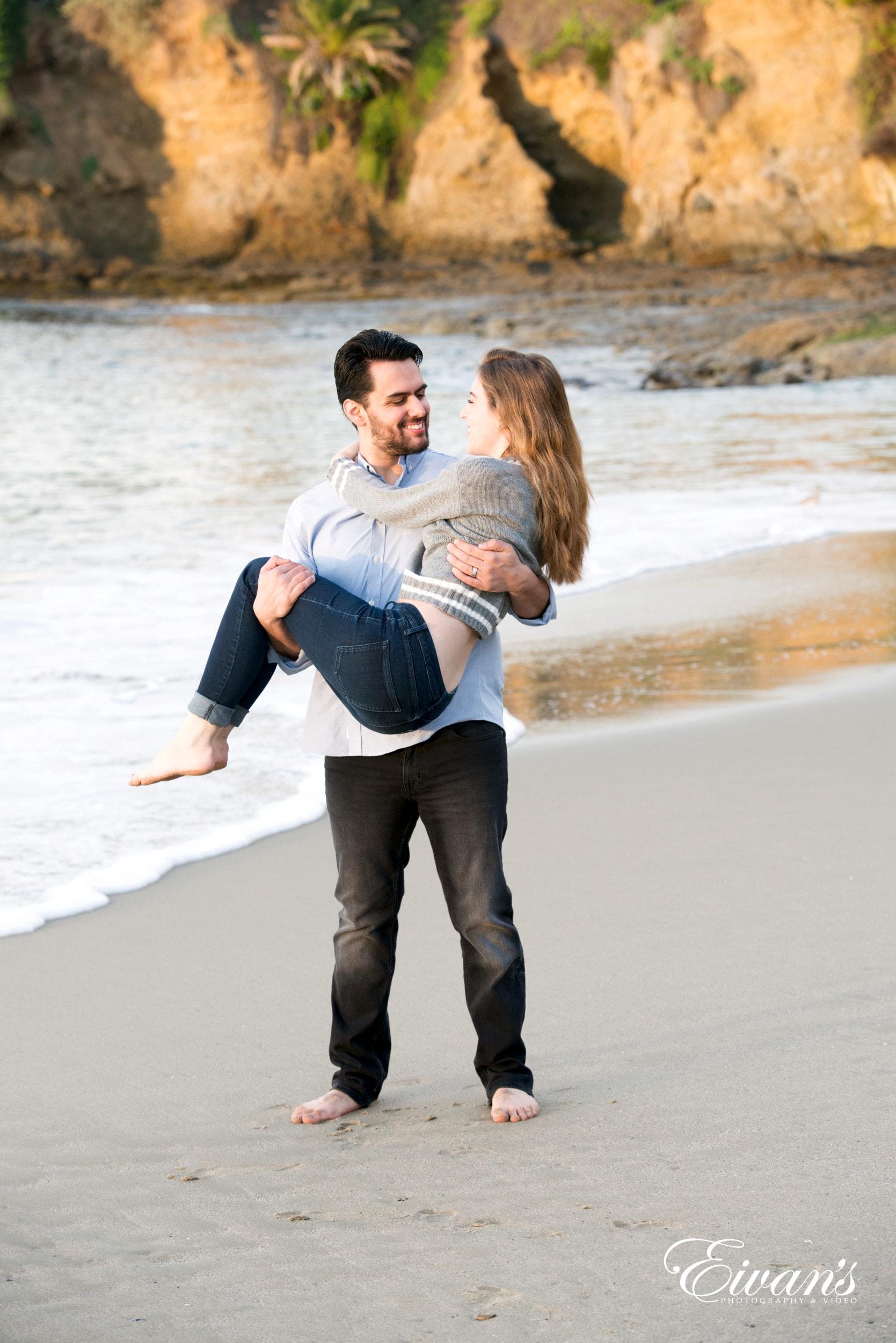 man in white long sleeve shirt hugging woman in white long sleeve shirt on beach during