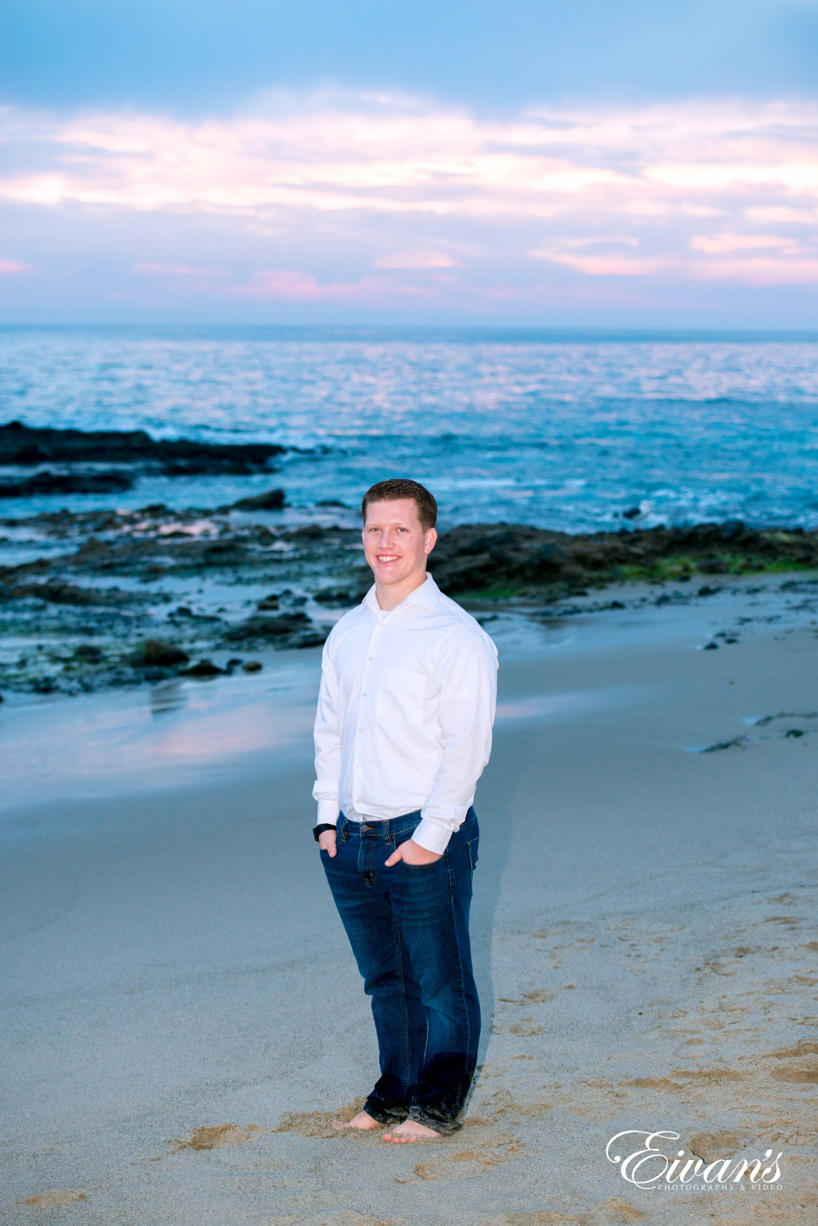 man in white dress shirt and blue denim jeans standing on beach shore during daytime