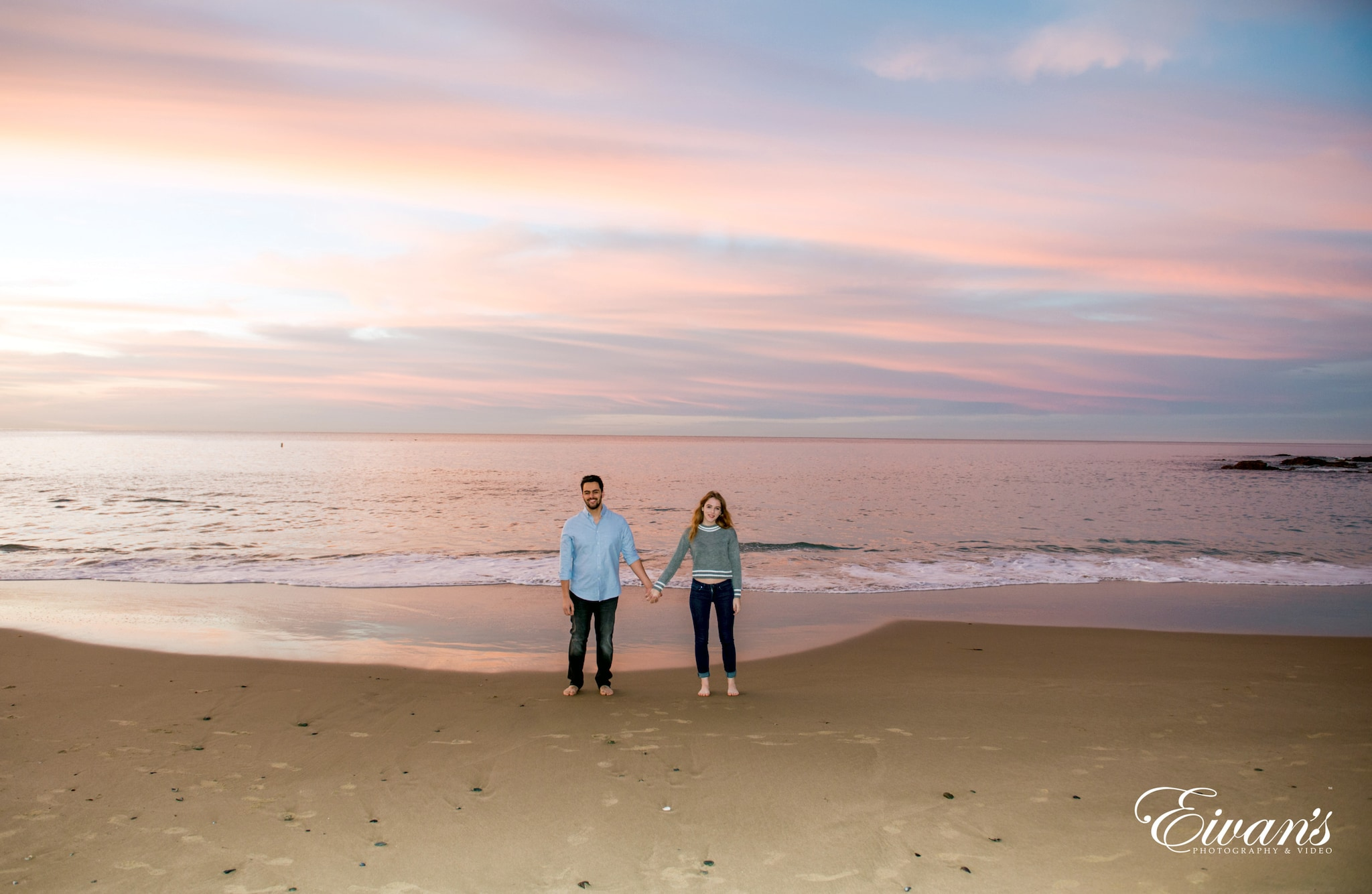 man and woman standing on beach during sunset