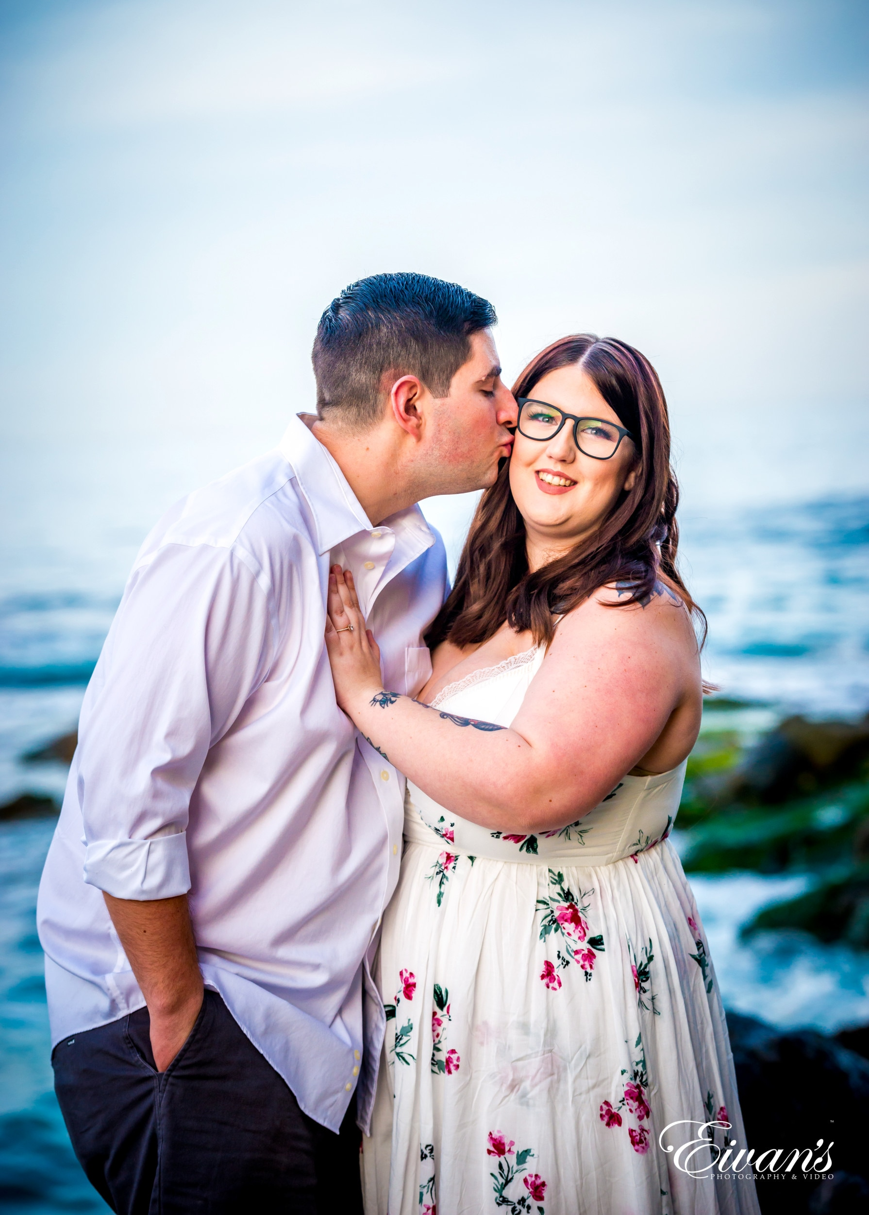 man in white dress shirt kissing woman in white and pink floral dress