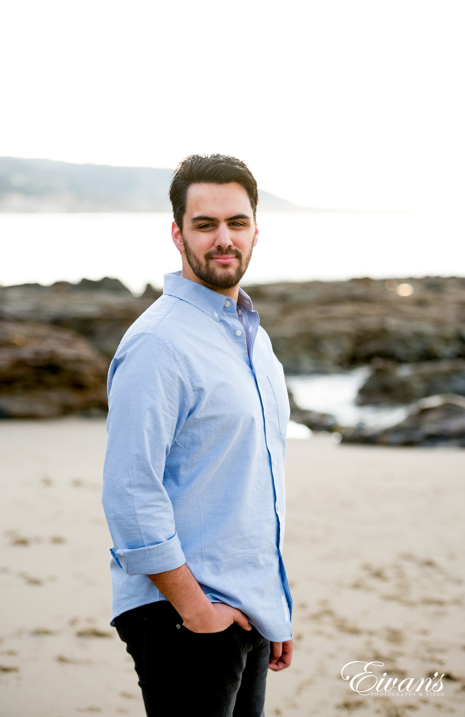 man in gray dress shirt standing on white sand during daytime