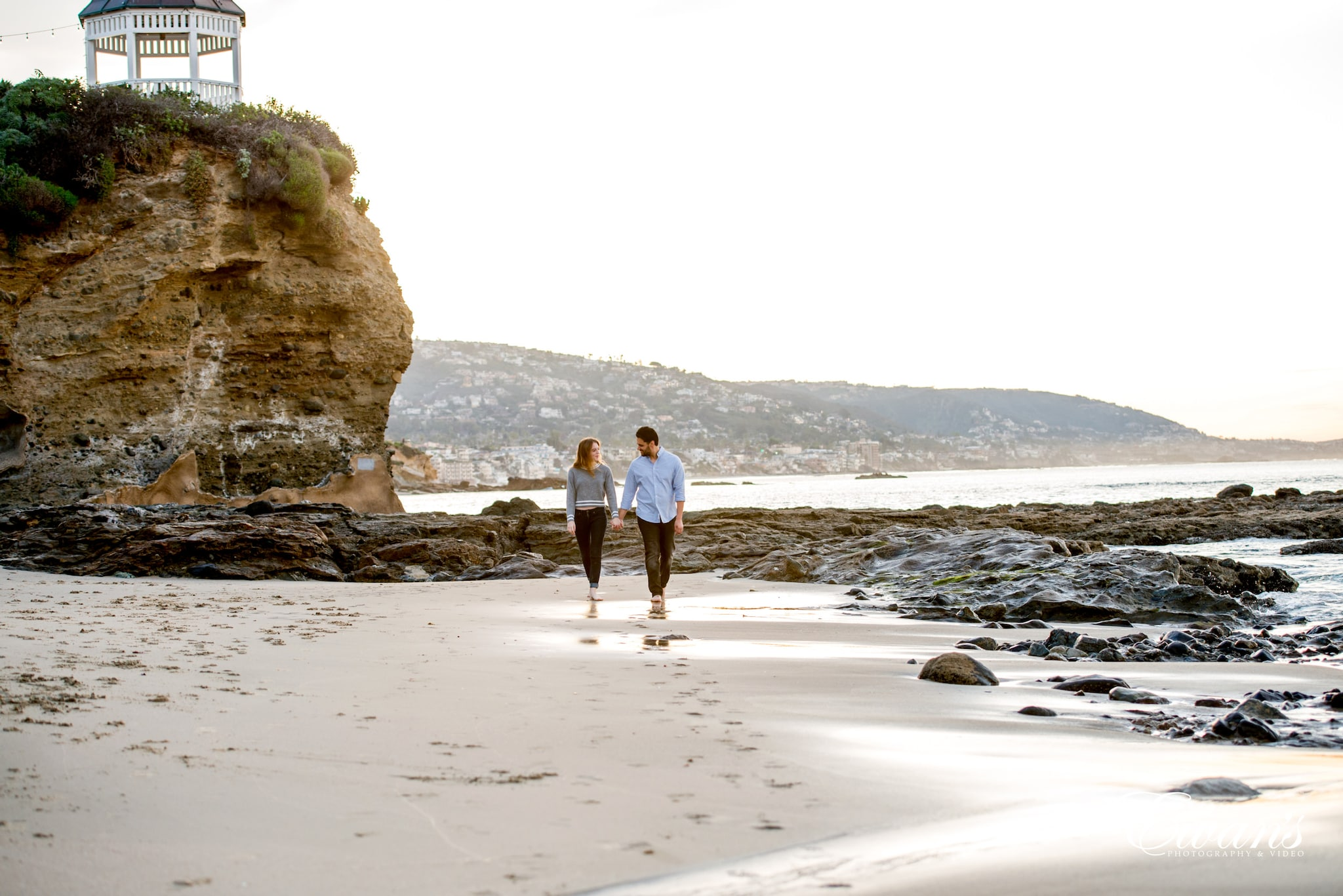 couple walking on beach during daytime