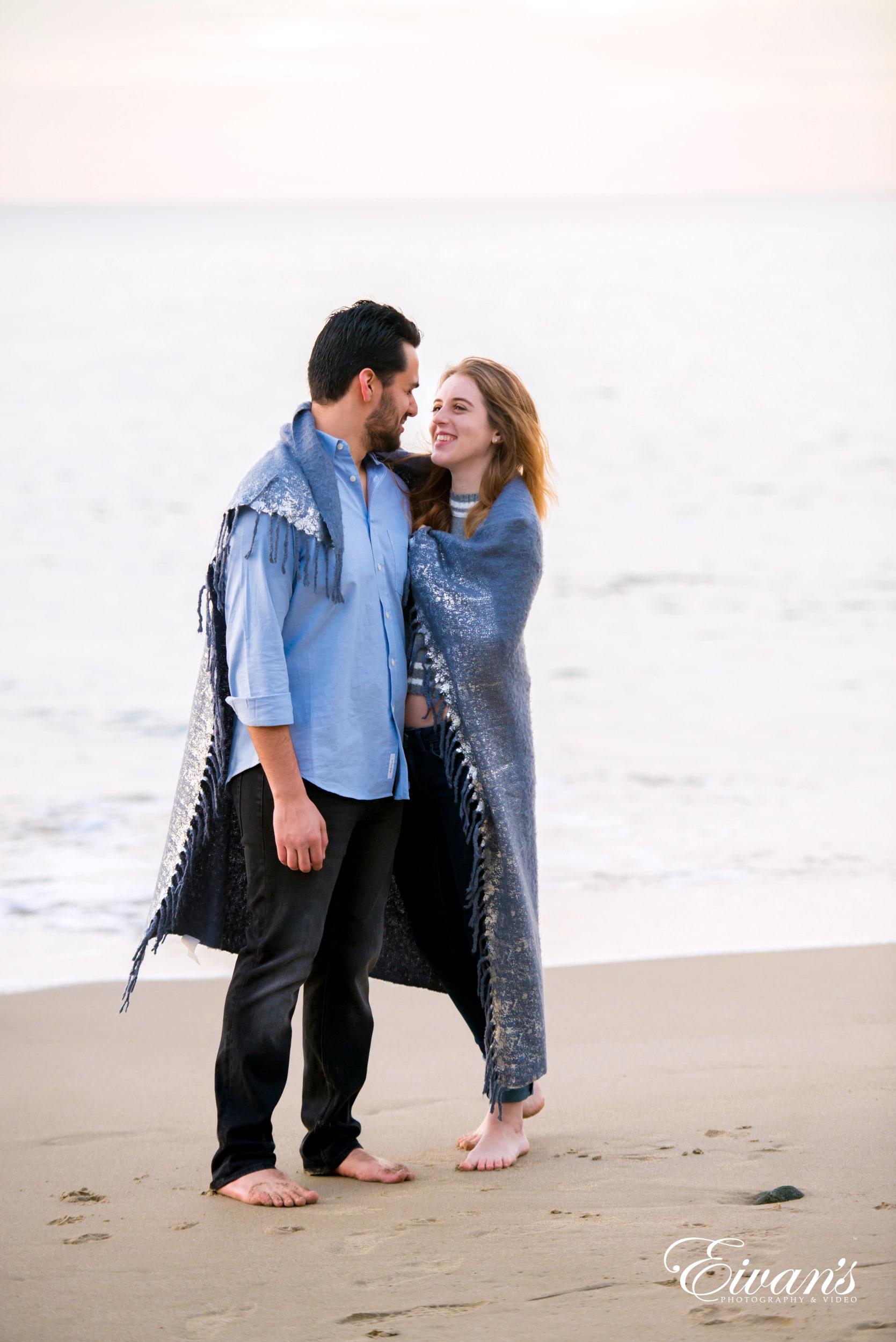 man in blue denim jacket hugging woman in black pants on beach during daytime