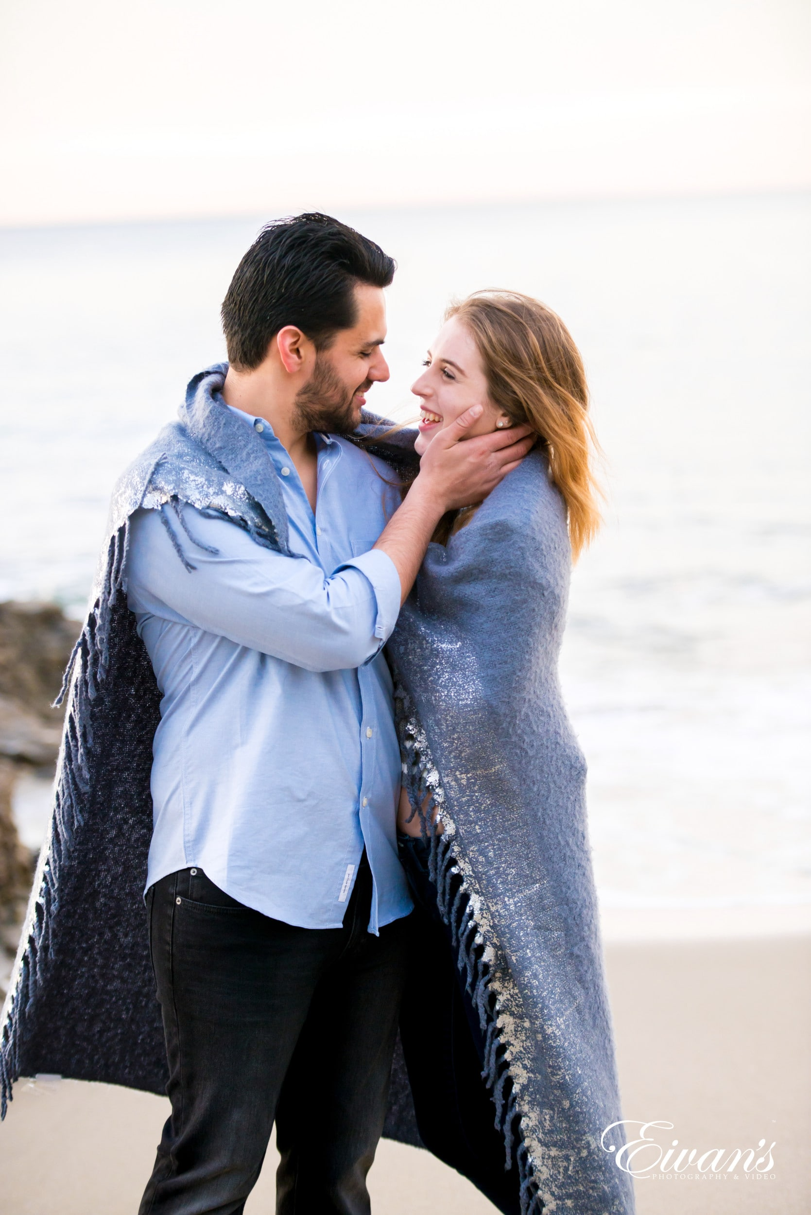 man in blue dress shirt kissing woman in black leather jacket on beach during daytime