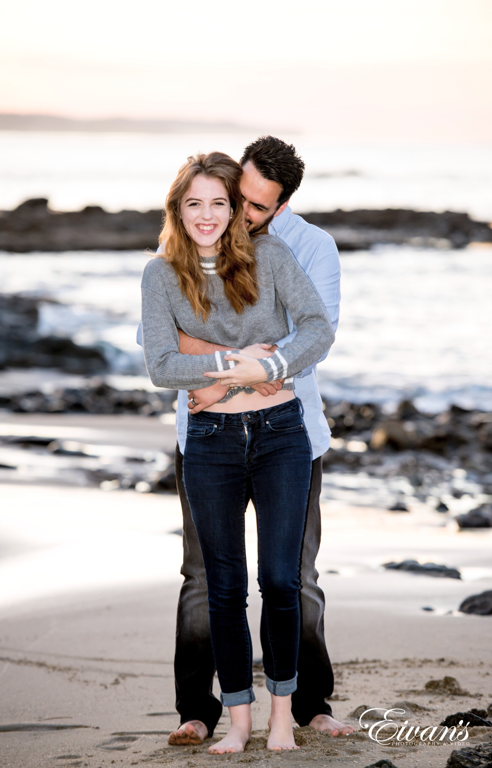 man in gray sweater hugging woman in gray sweater on white sand during daytime