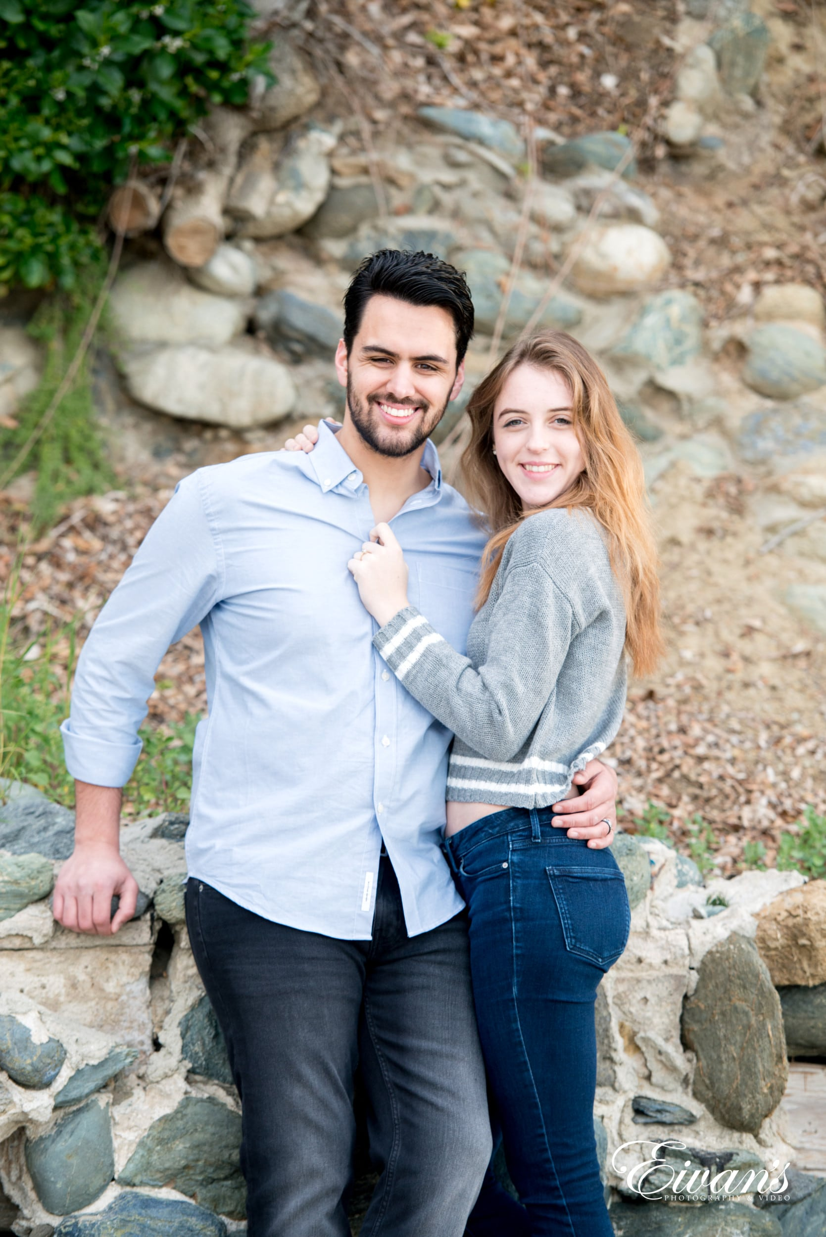 man in gray dress shirt hugging woman in blue denim jeans
