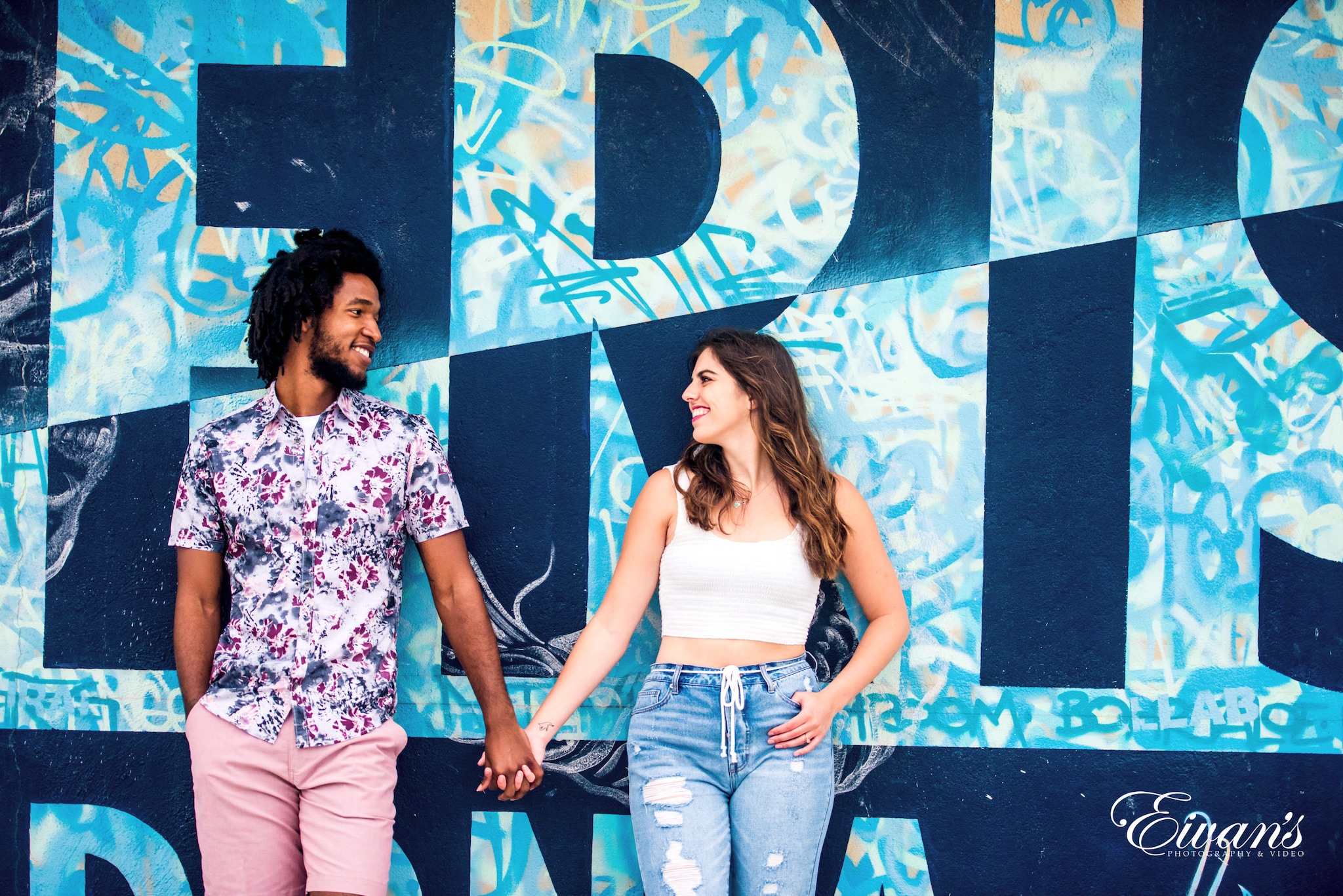 woman in white and pink floral shirt and blue denim jeans standing beside wall with graffiti