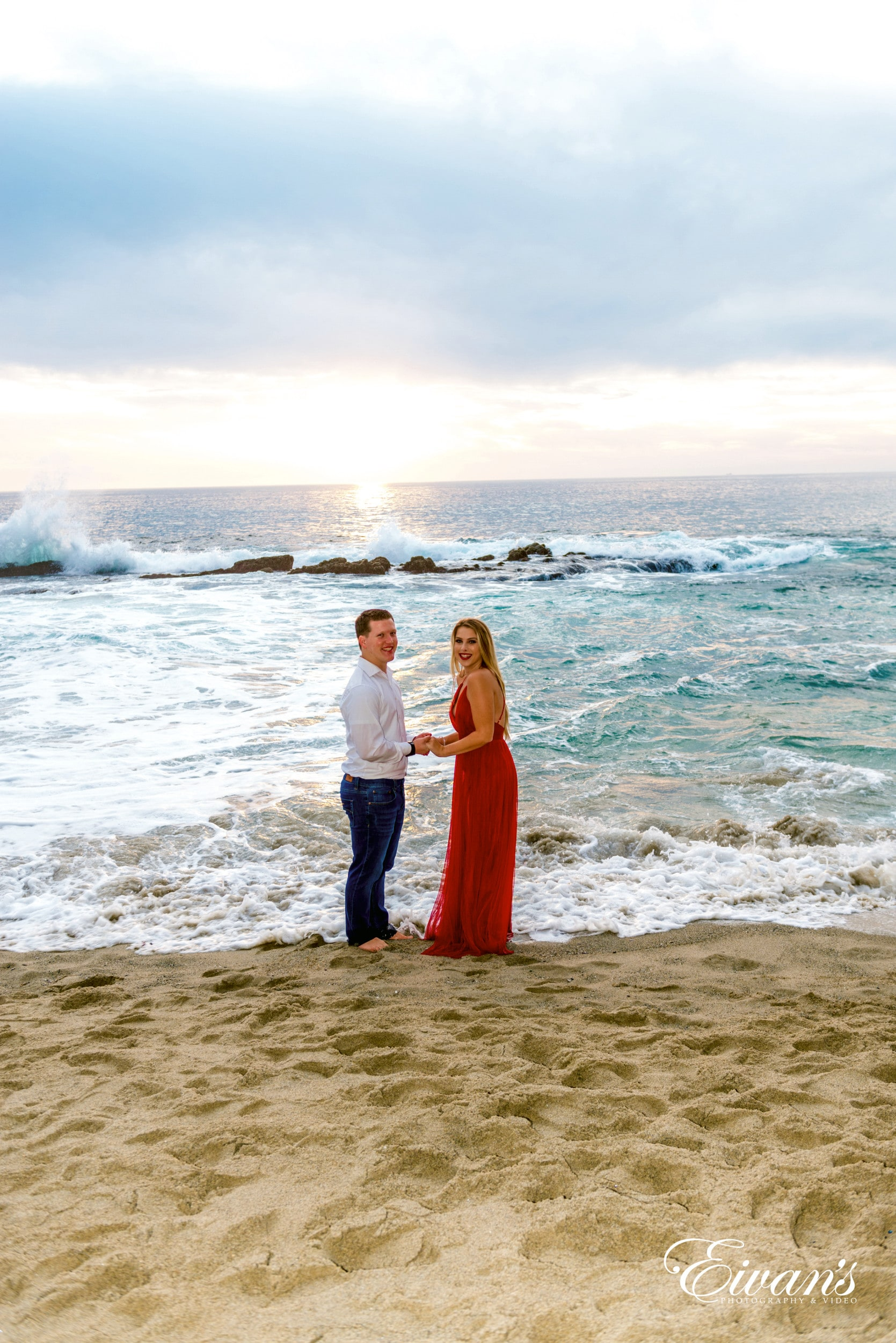 woman in red dress standing beside man in white dress shirt on beach during daytime