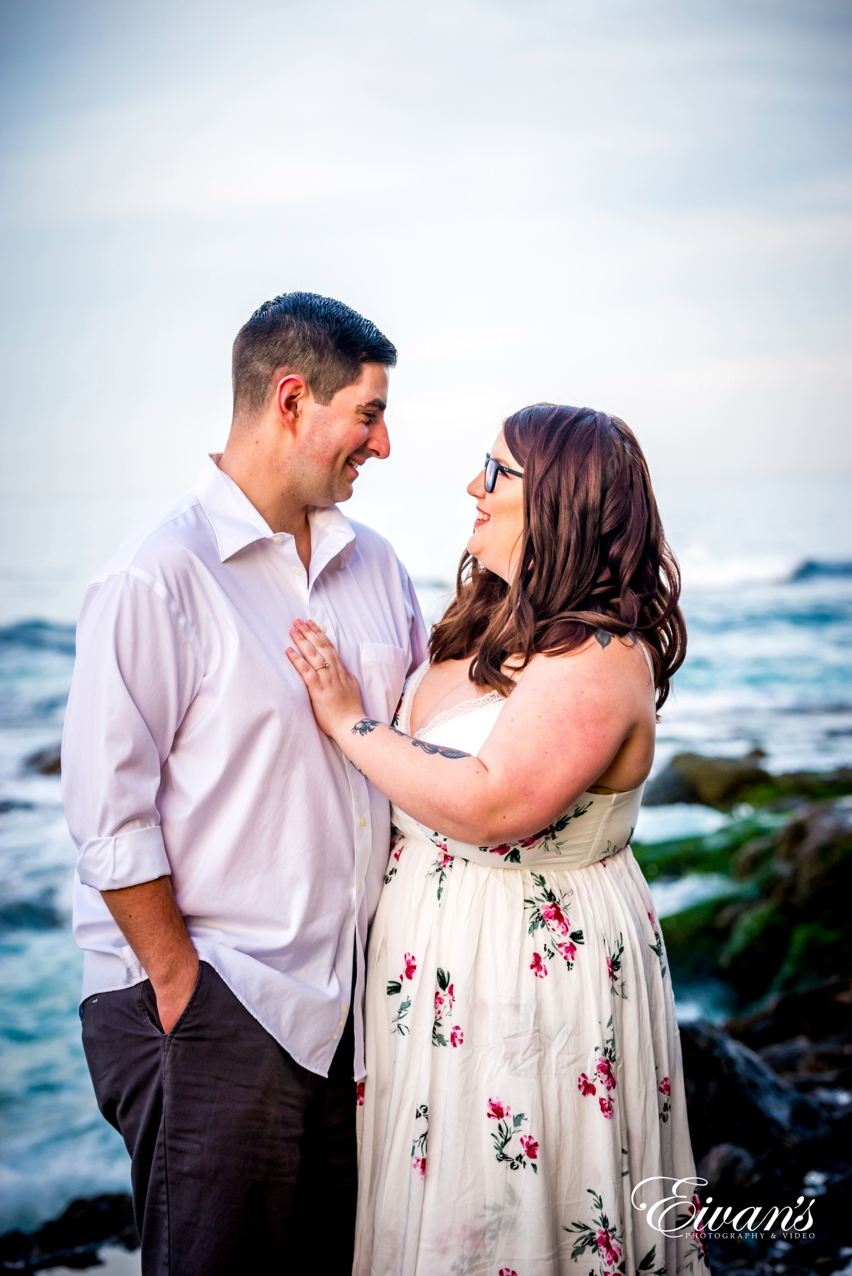 man in white dress shirt kissing woman in white floral dress