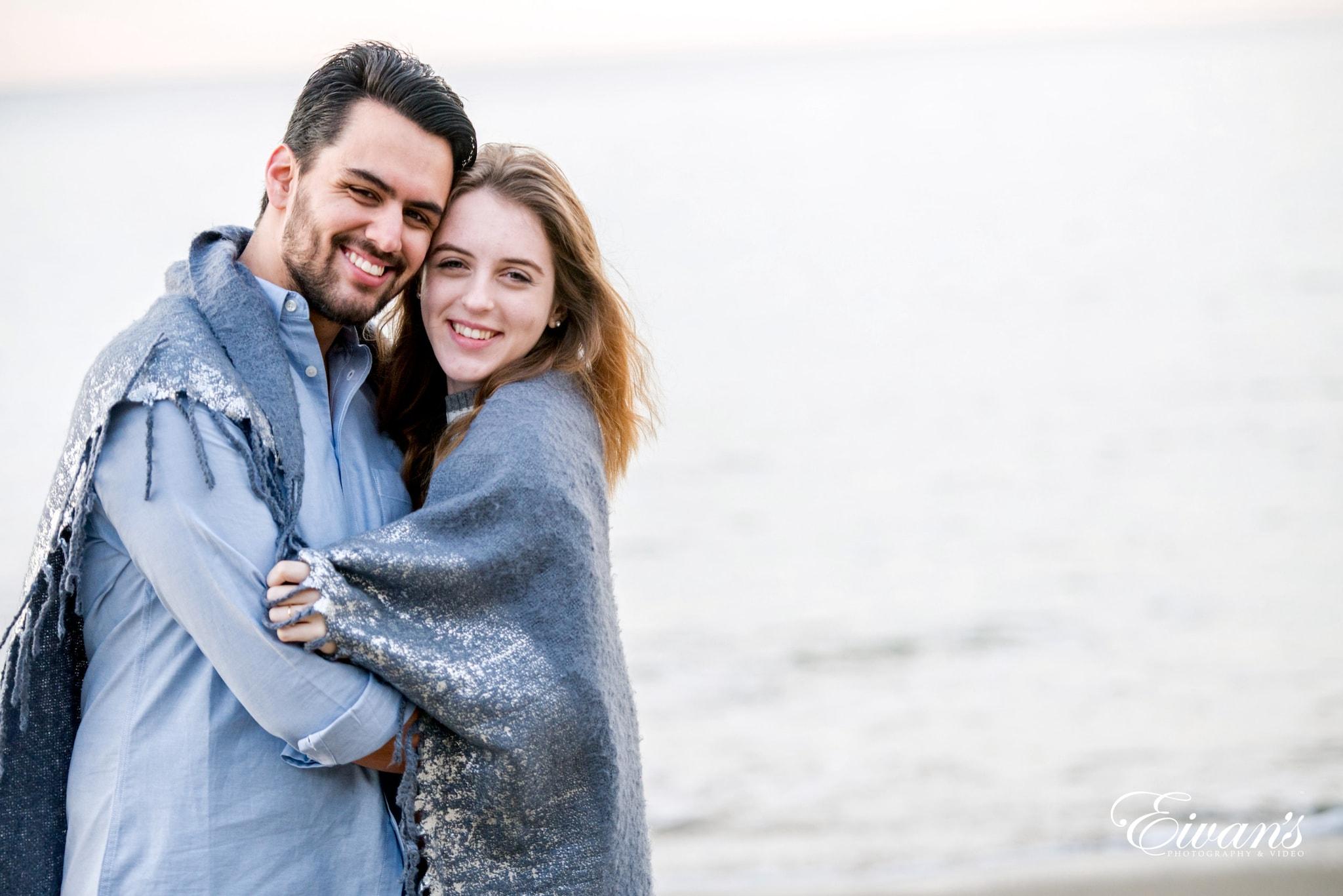 man in blue denim jacket hugging woman in gray sweater