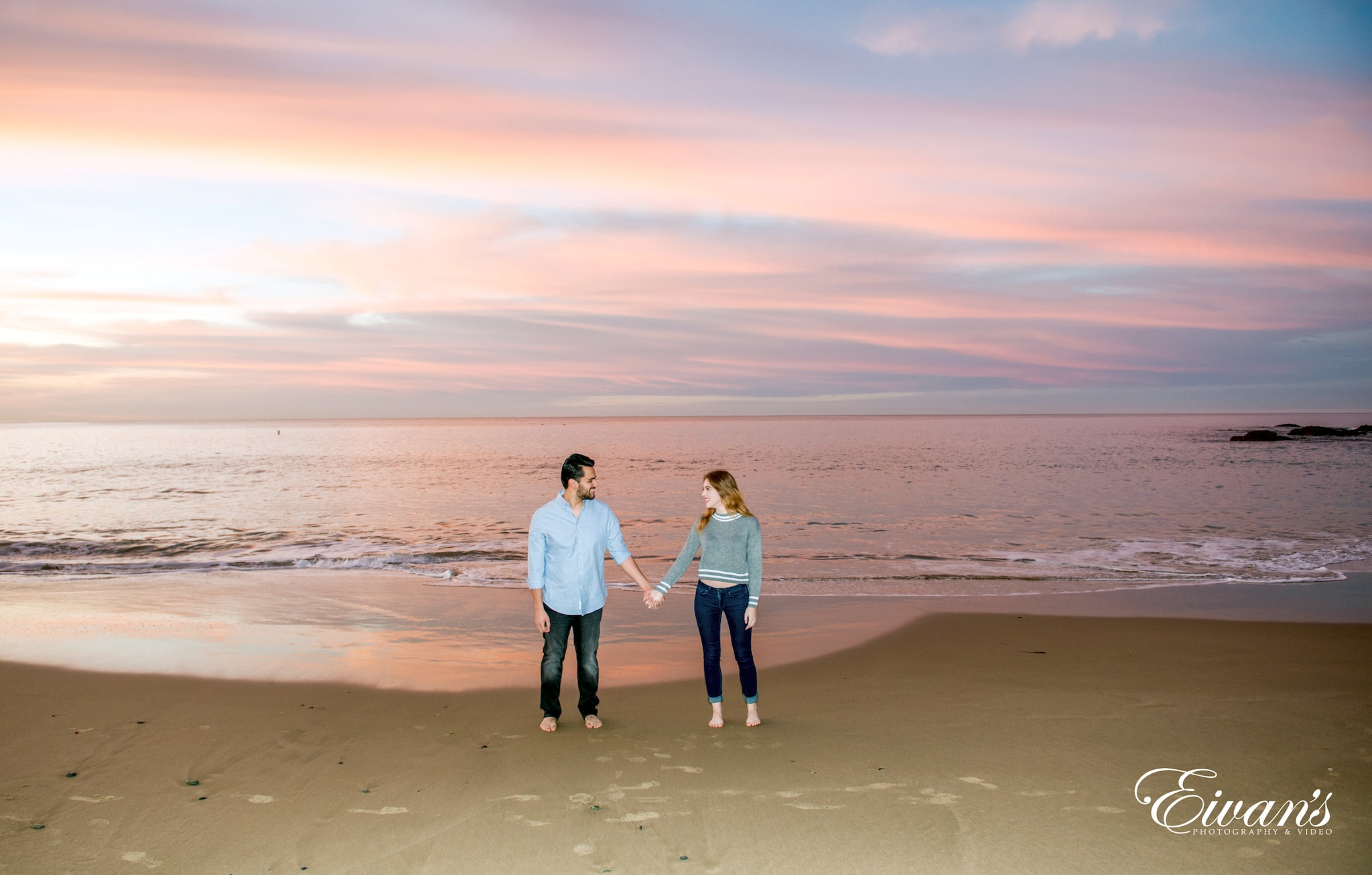 couple standing on beach during sunset