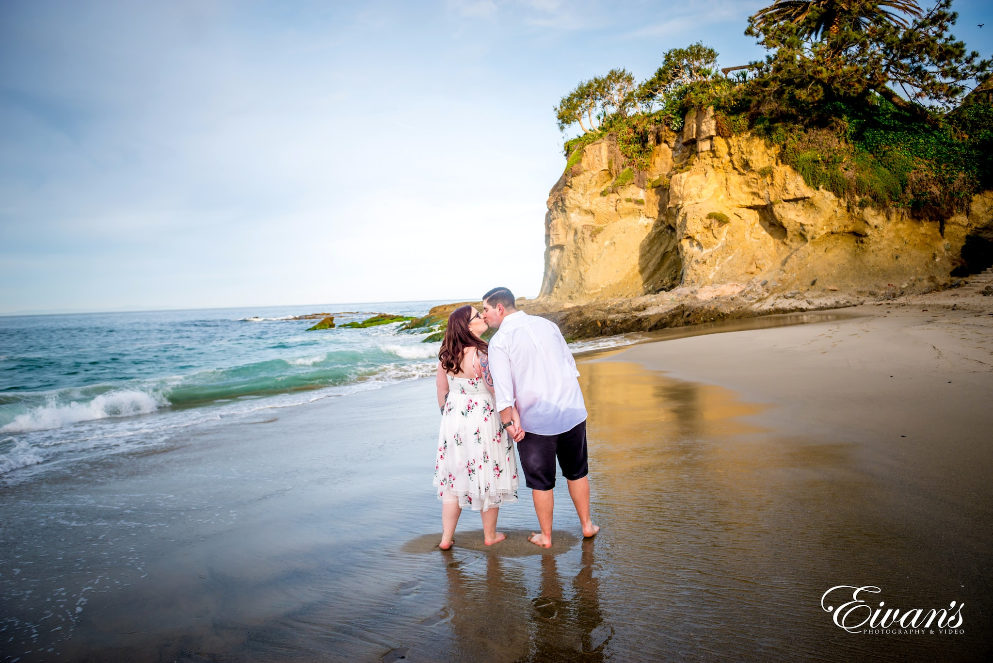 couple standing on beach during daytime
