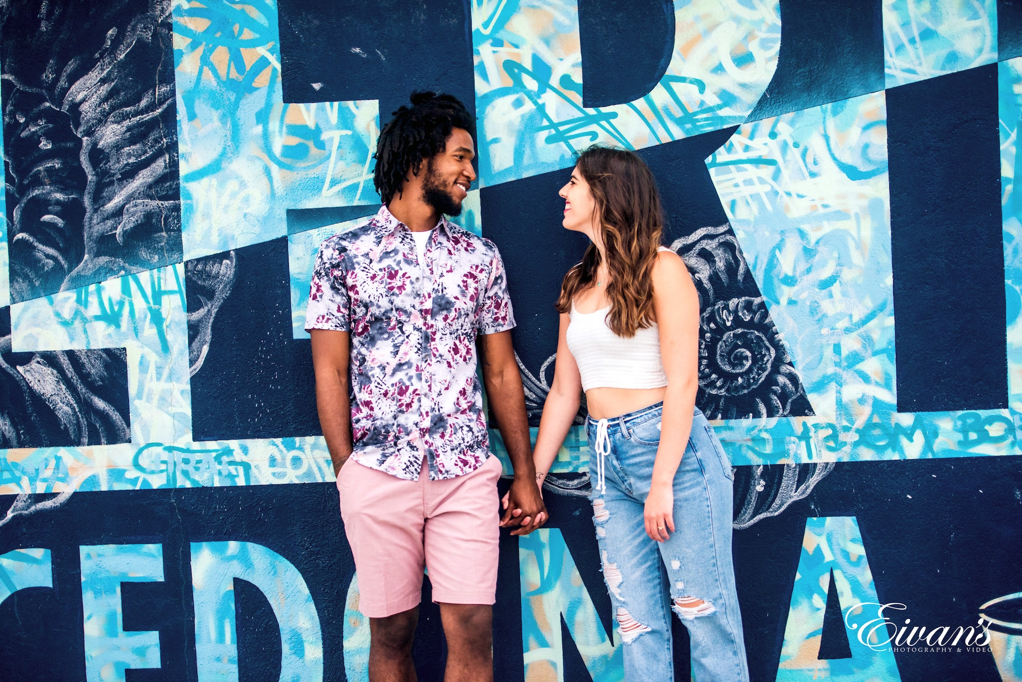 man and woman standing beside wall with graffiti