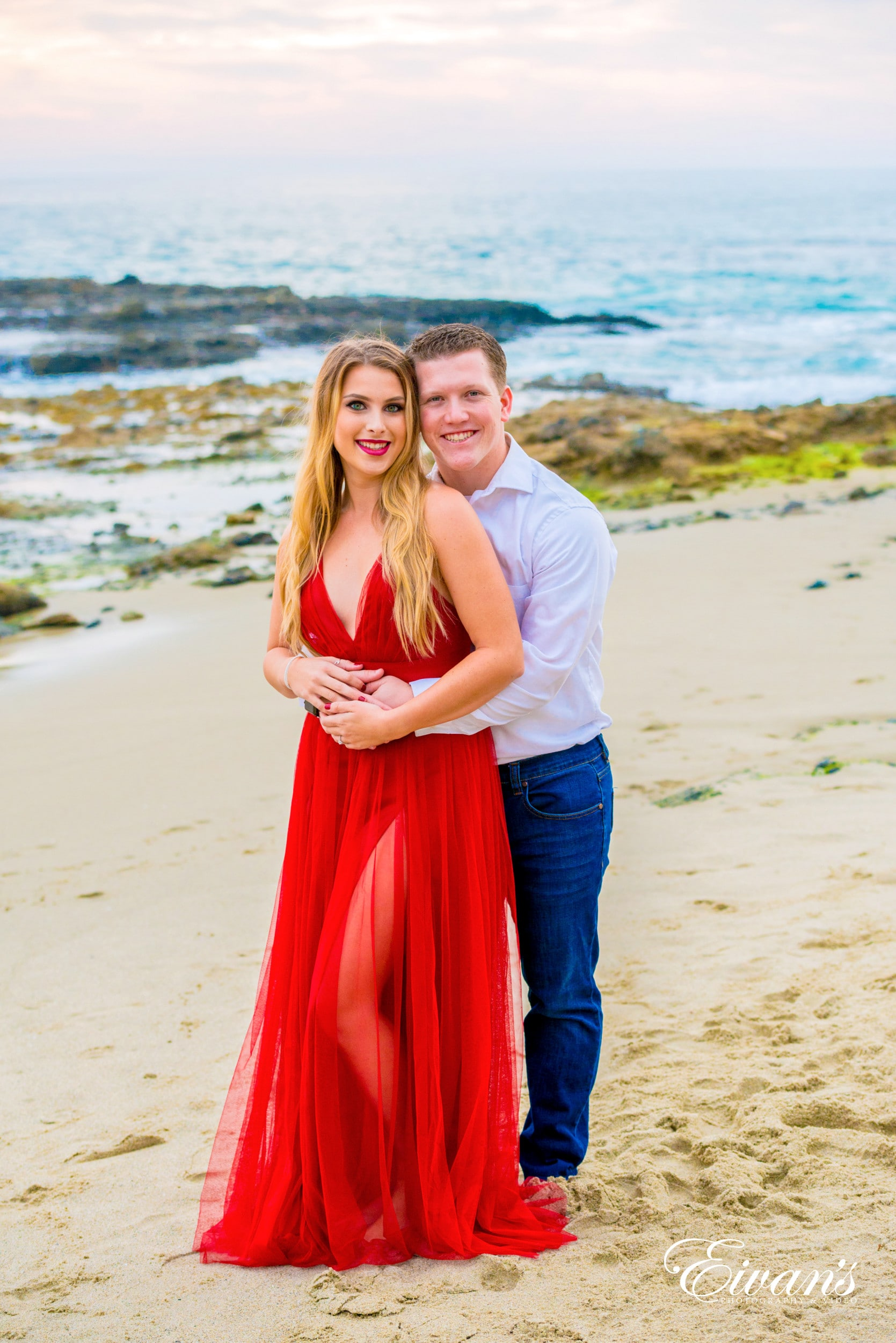 woman in red dress standing beside man in white t-shirt on beach during daytime
