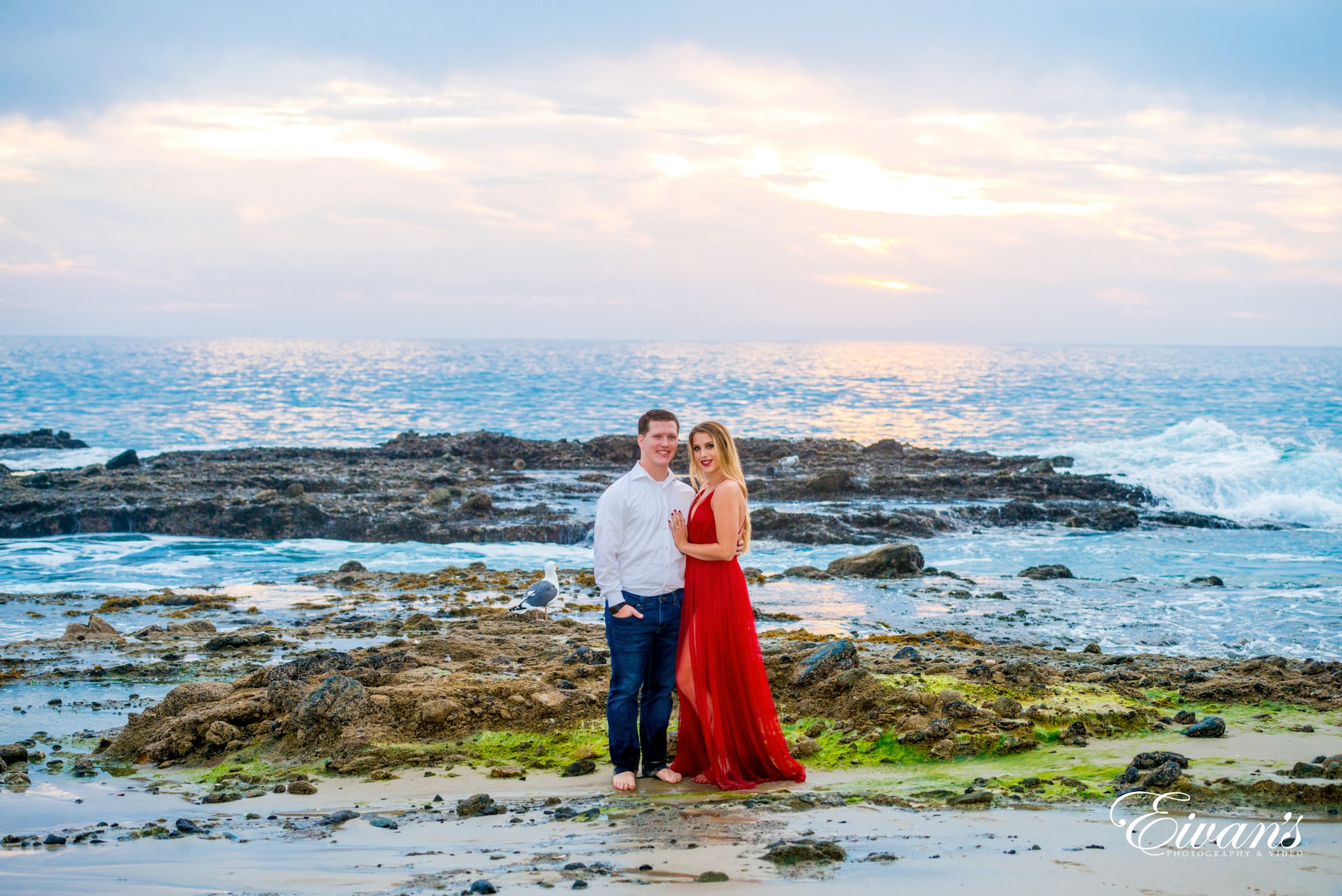 woman in red dress standing beside man in white dress shirt on seashore during daytime