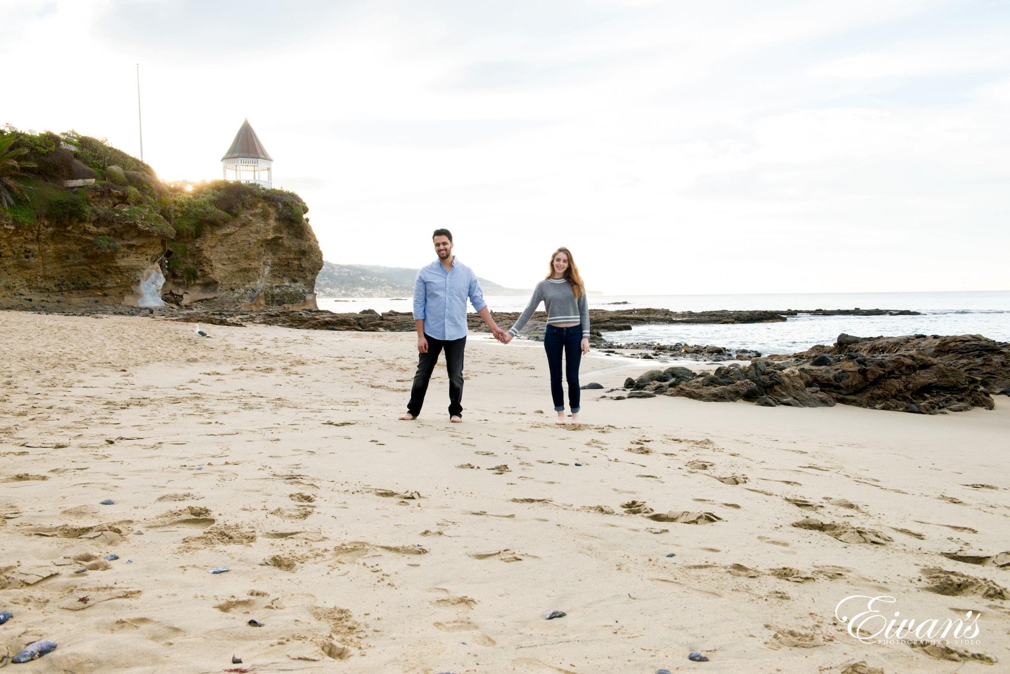 couple walking on beach during daytime