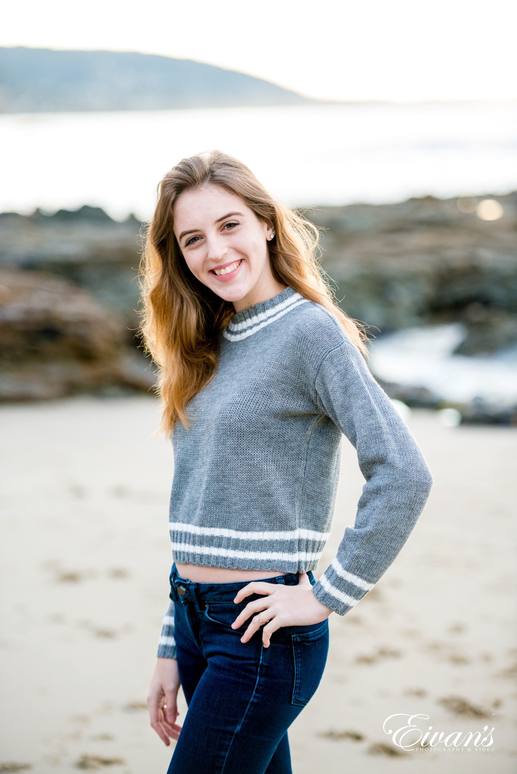 woman in gray long sleeve shirt and blue denim jeans standing on beach during daytime