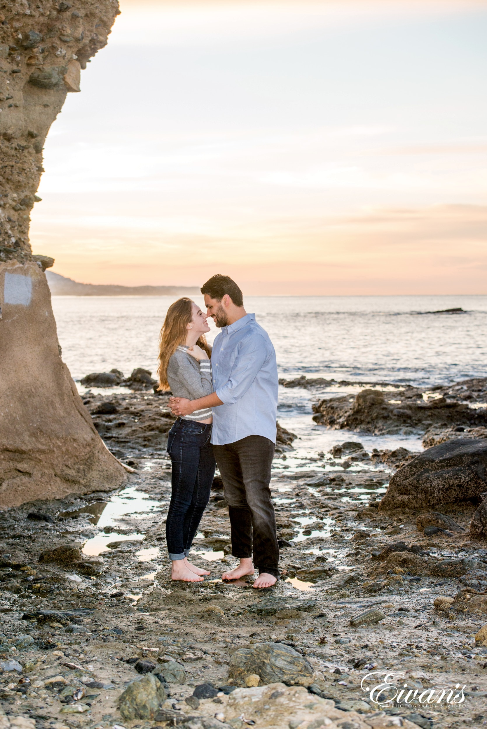 couple standing on rocky shore during daytime