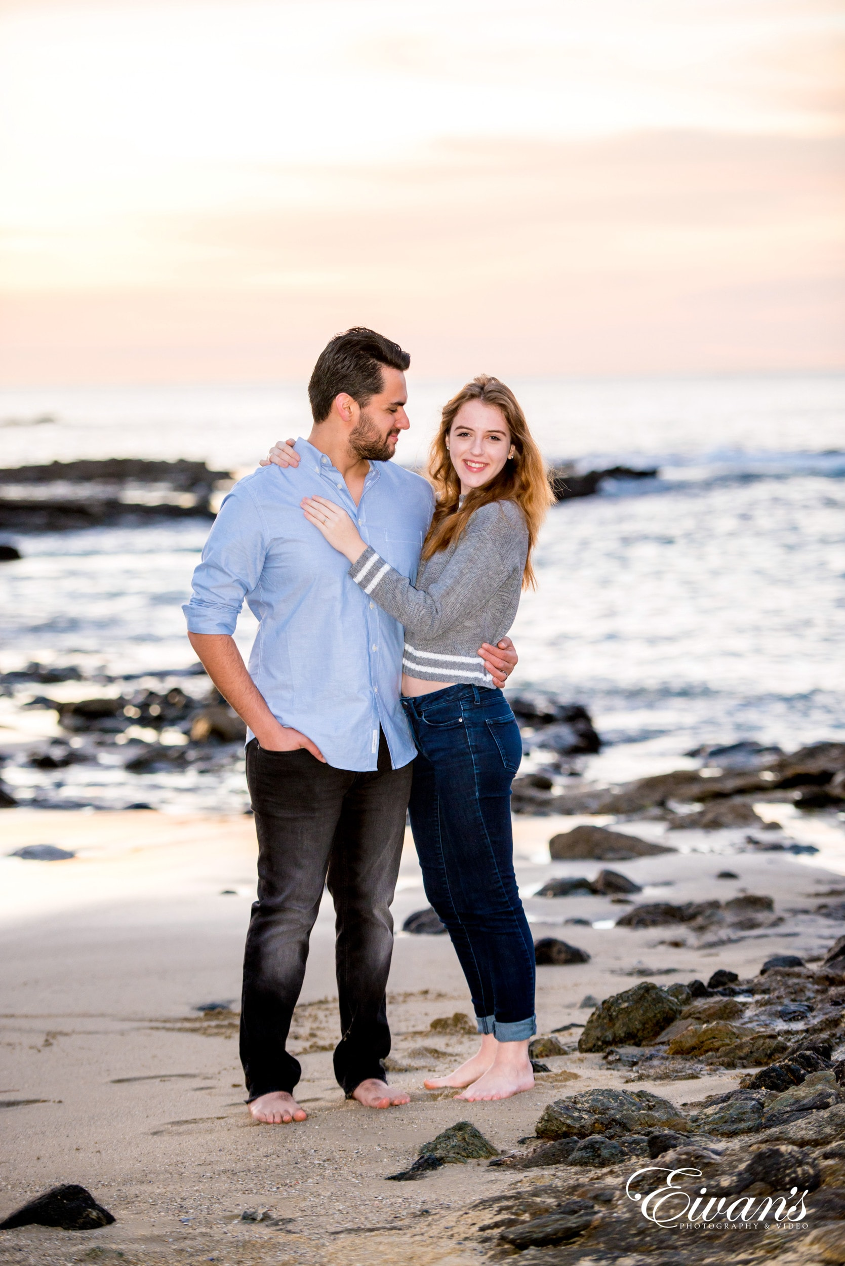 man in blue dress shirt hugging woman in white long sleeve shirt on beach during daytime