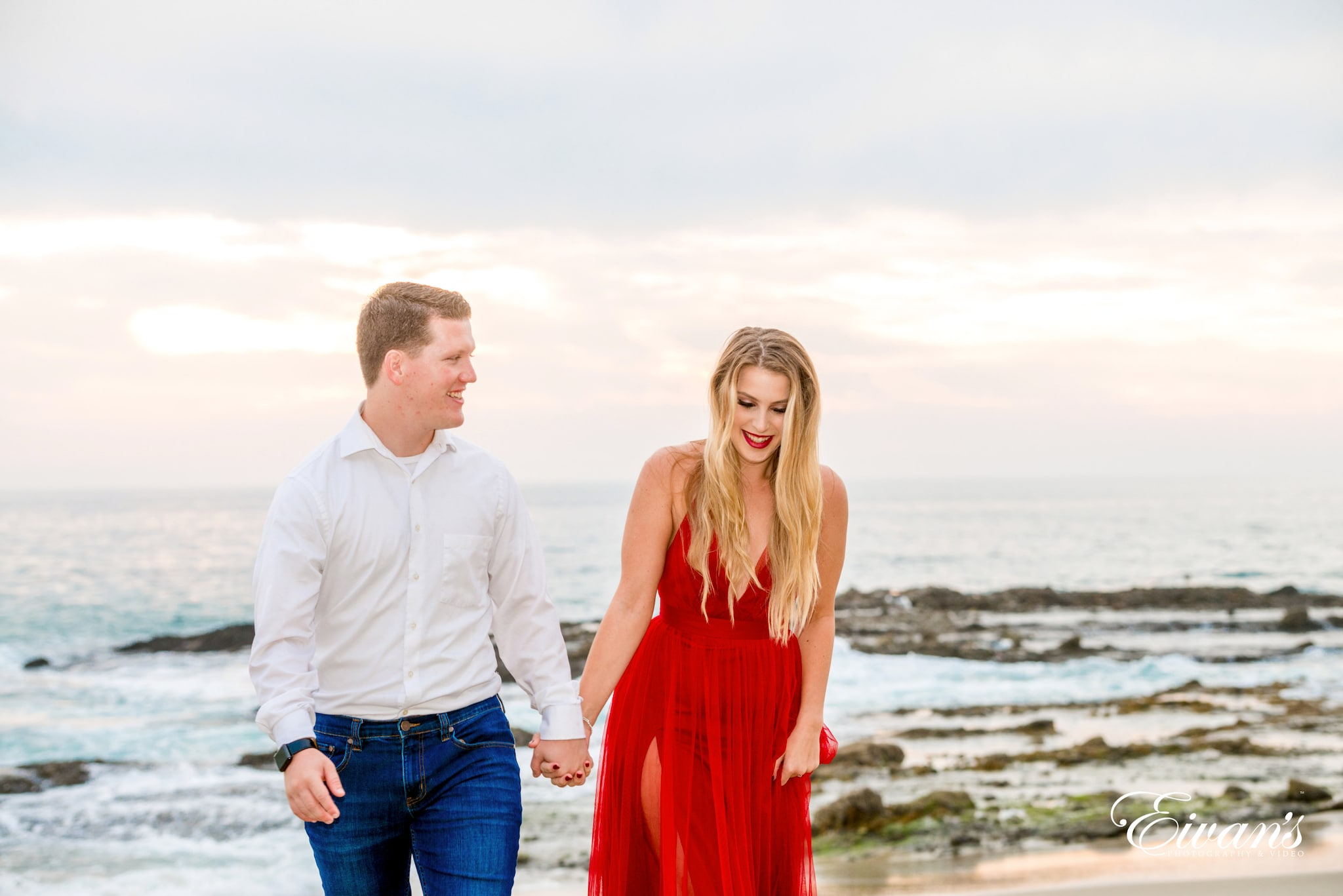 man in white dress shirt and woman in red dress standing on beach during daytime