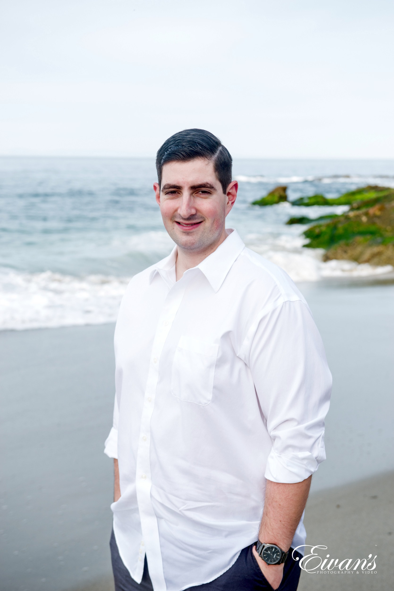 man in white dress shirt standing on beach during daytime