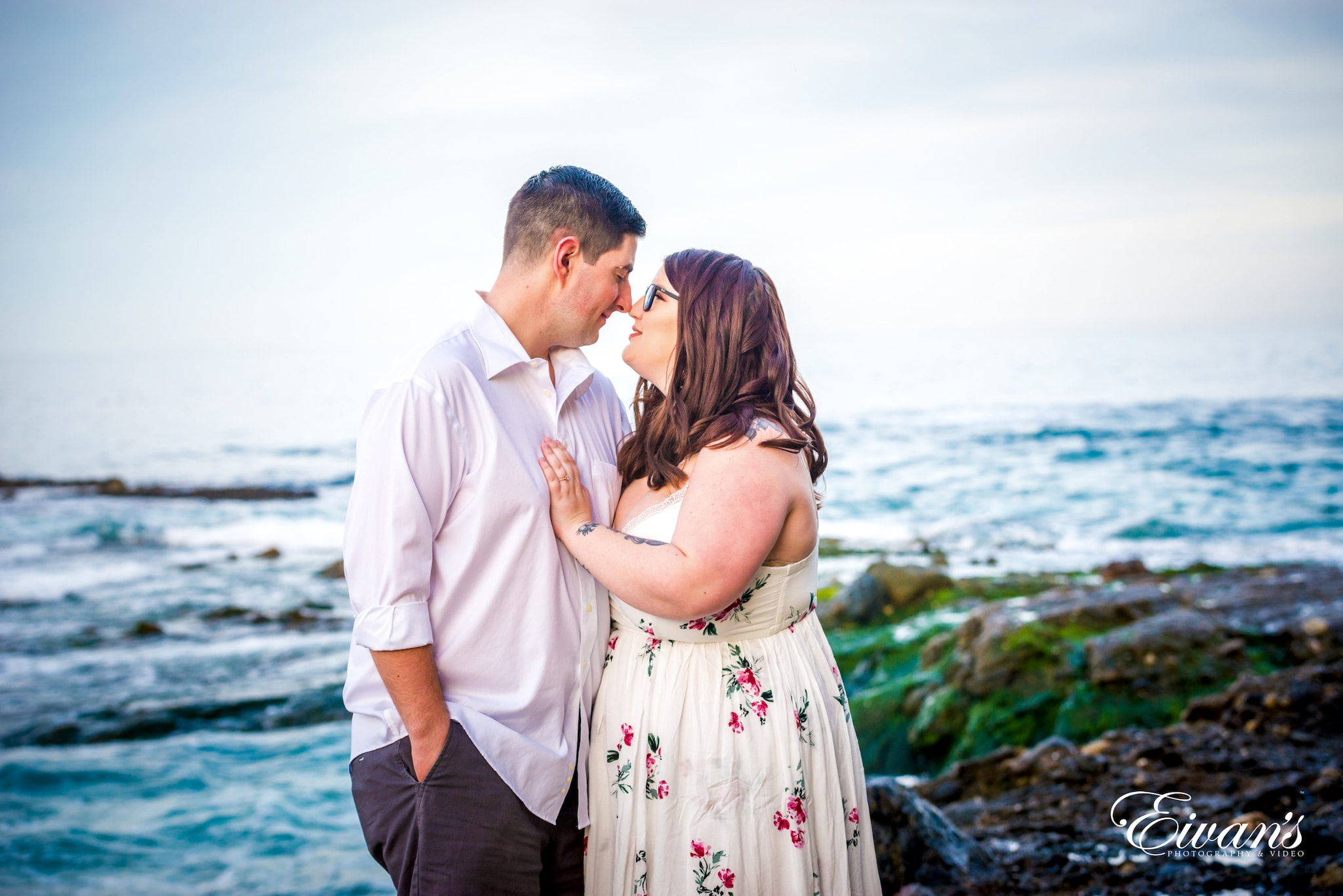 man and woman kissing near body of water during daytime